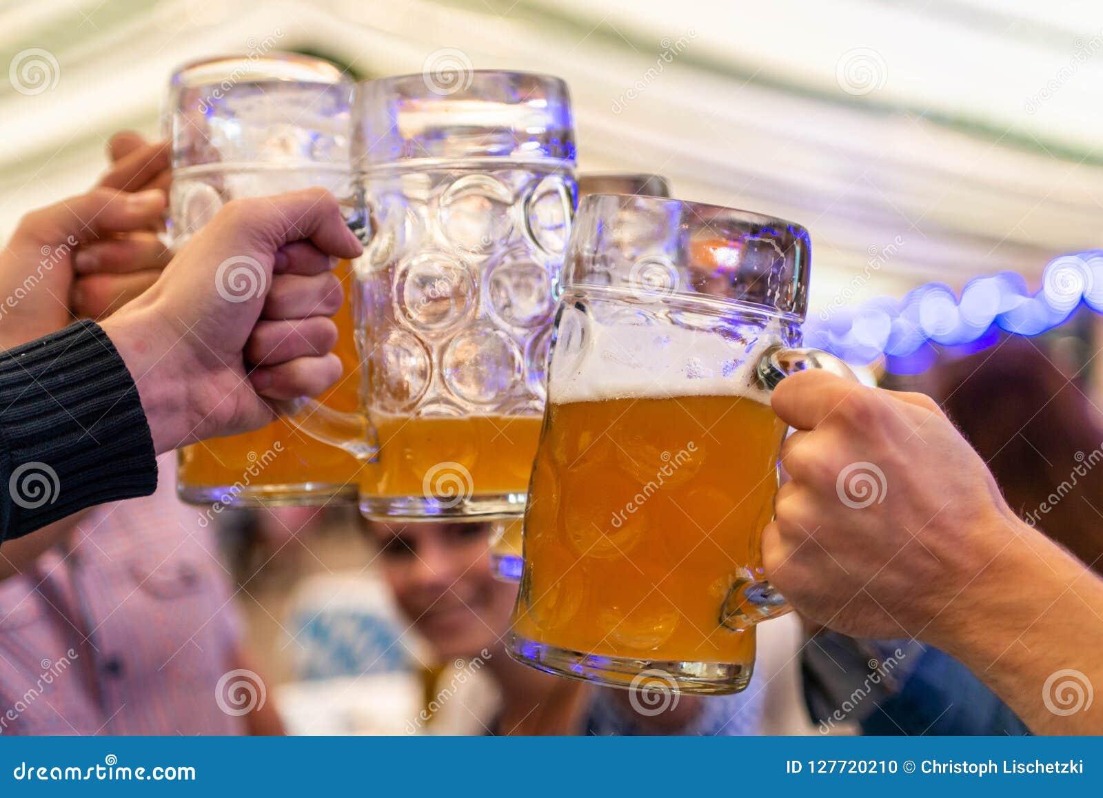 Een groep jongerenvrienden die met glazen bier bij de Zachte nadruk van Oktoberfest roosteren Duitsland Ondiepe DOF