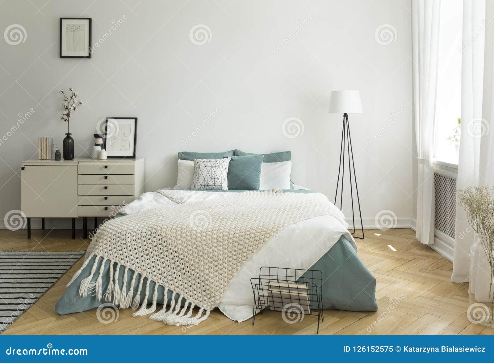 Een groot comfortabel bed met bleke wijze groene en witte linnen, hoofdkussens en deken in een binnenland van de vrouwen` s helde