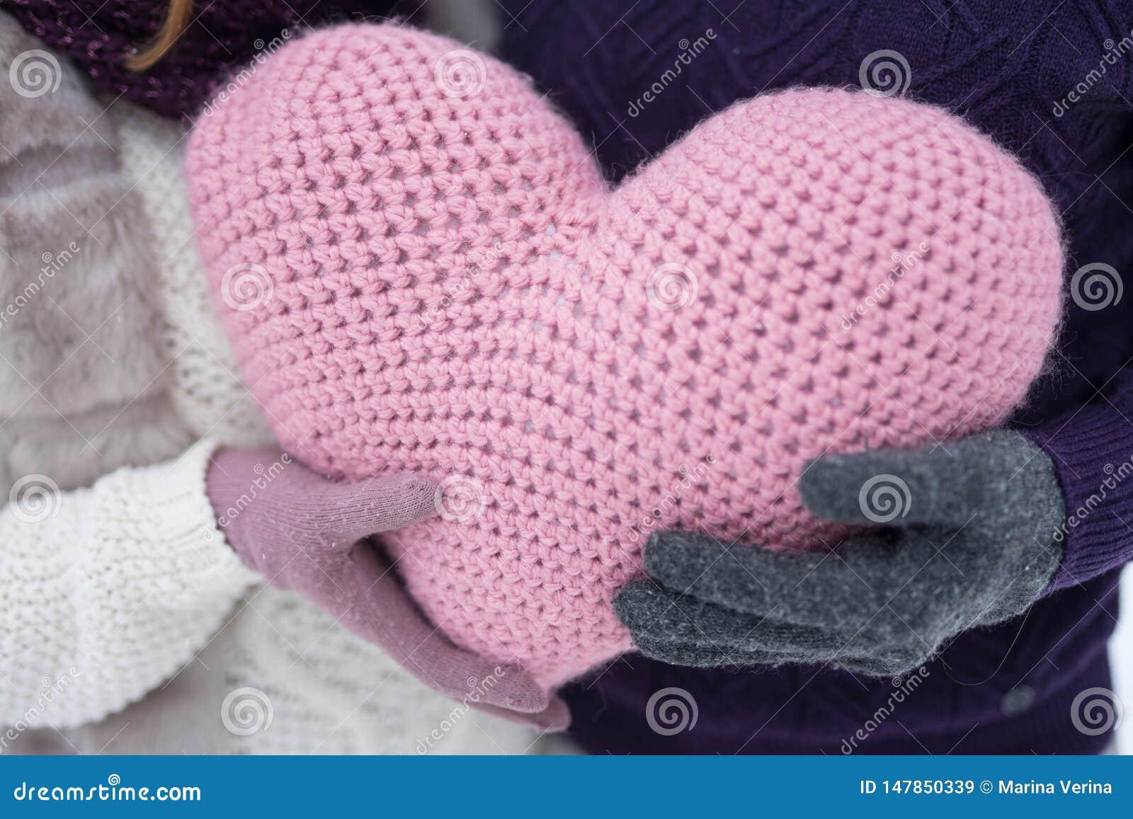 Een groot roze hart in de handen van een man en een vrouw