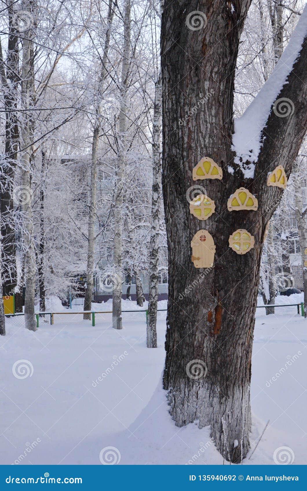 Een grote boomstam van snow-covered hout waarop van triplex ronde, gesneden Vensters en deuren voor kinderen om worden gemaakt te