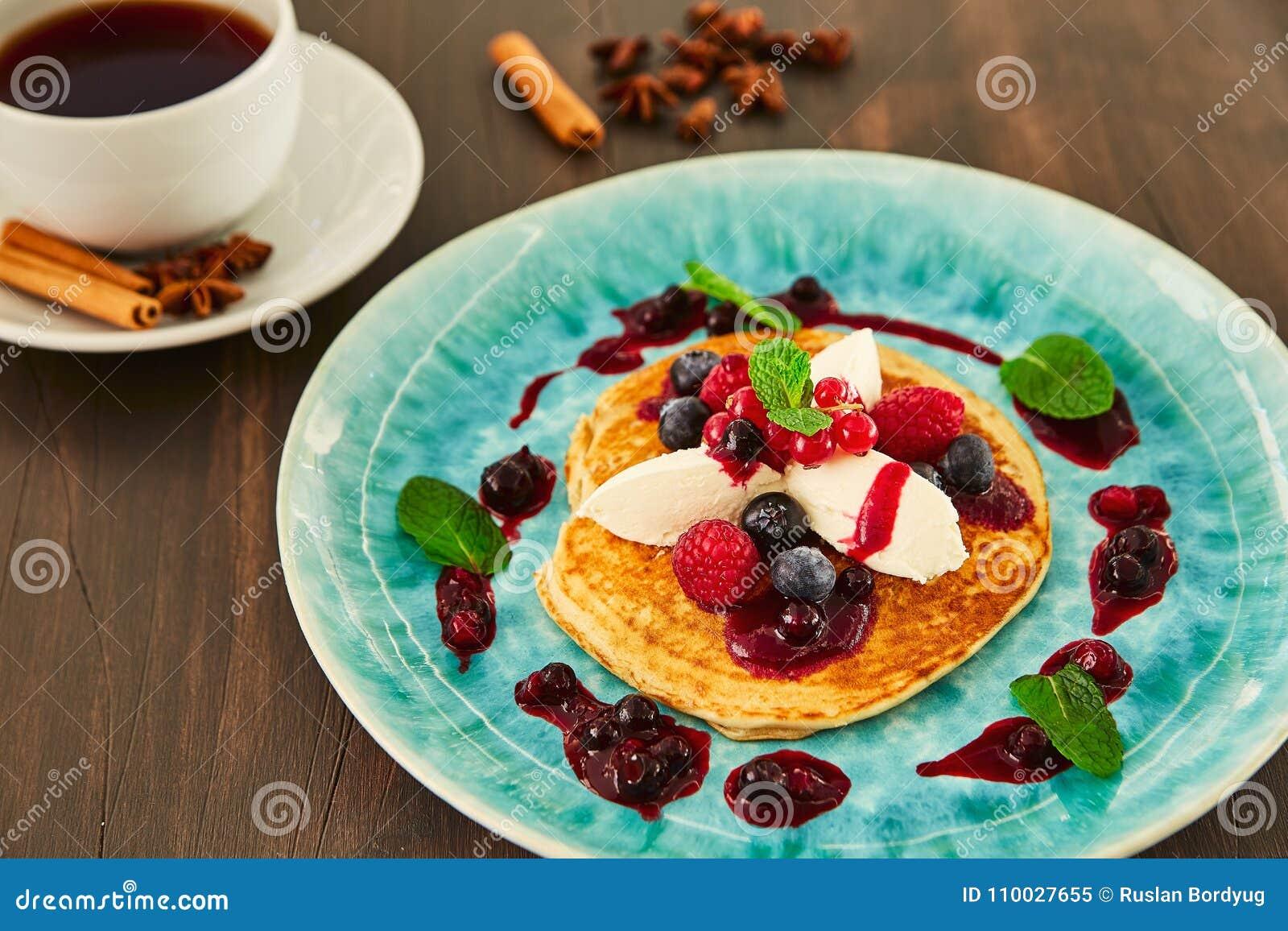 Een grote eigengemaakte pannekoek met witte mascarponeroom, frambozen, bosbessen, bessen, bessen en honing op een blauwe plaat He