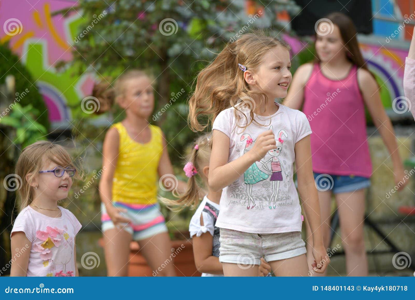 Een grote groep het gelukkige de jonge geitjes van pretsporten springen, sporten en het dansen Kinderjaren, vrijheid, geluk, het
