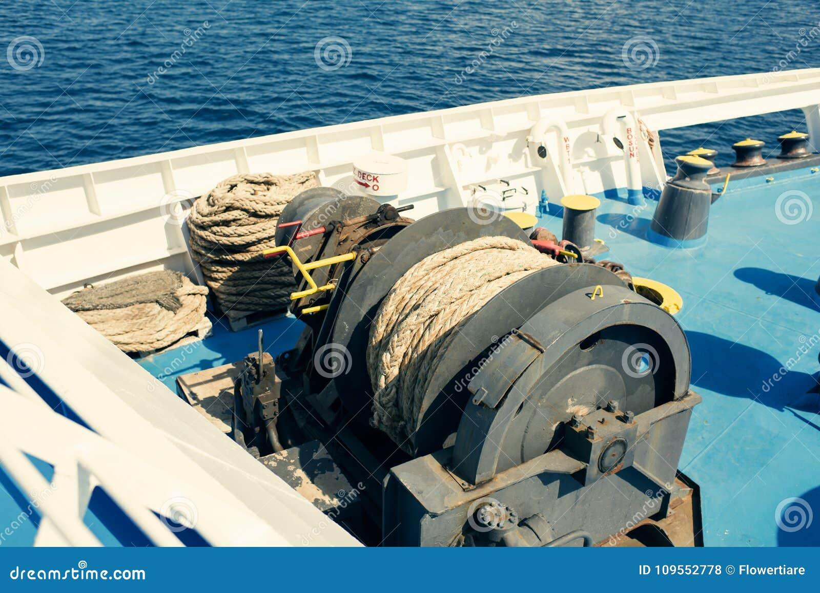 Een grote katrolschijf met gerolde tros op het open dek van de veerboot De zomercruise in Griekenland