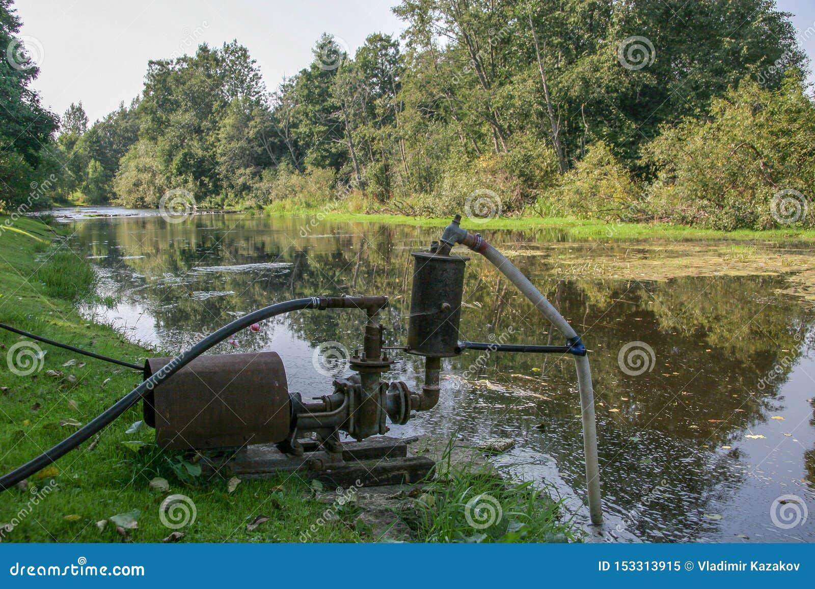 Een grote oude waterpomp bevindt zich op de bank van de rivier en het pompenwater