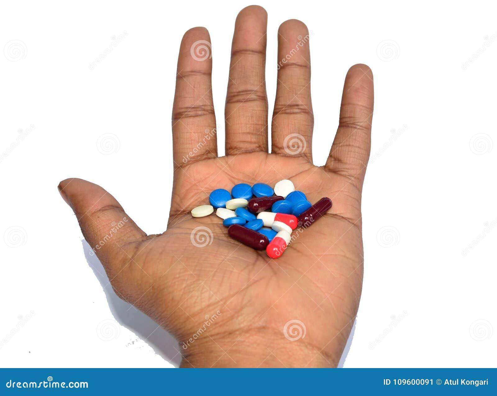 Een hand die kleurrijke pillen houden