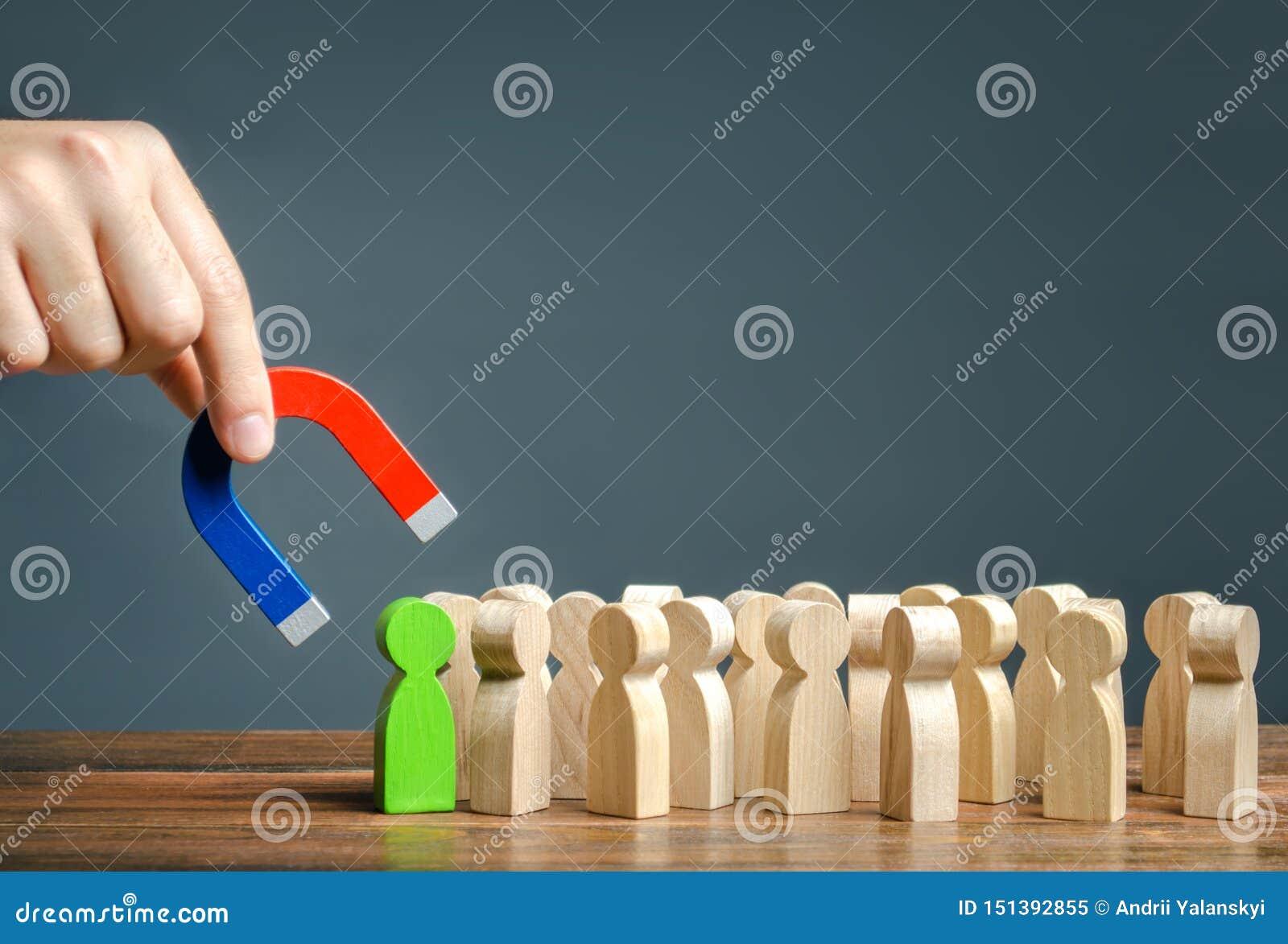 Een hand met een magneet probeert om een groen cijfer van een persoon uit een menigte te trekken Zoeken voor begaafde arbeiders m
