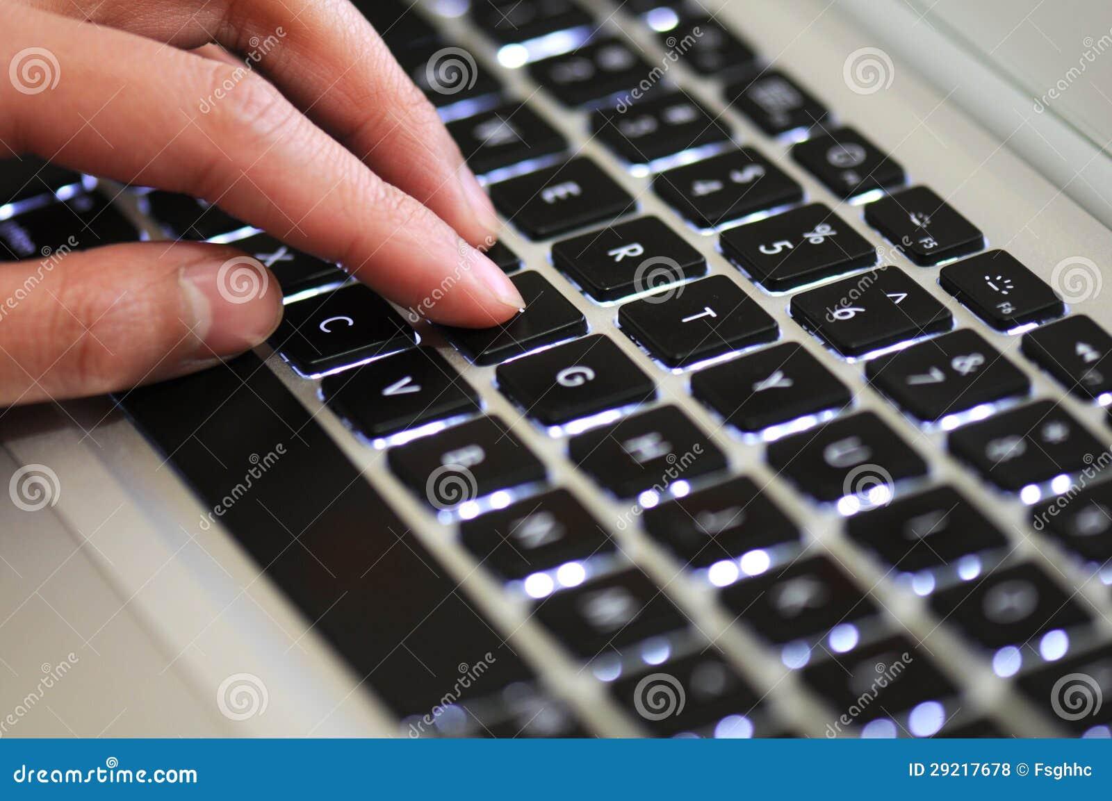 Toetsenbord Met Licht : Een hand op een toetsenbord met licht stock foto afbeelding