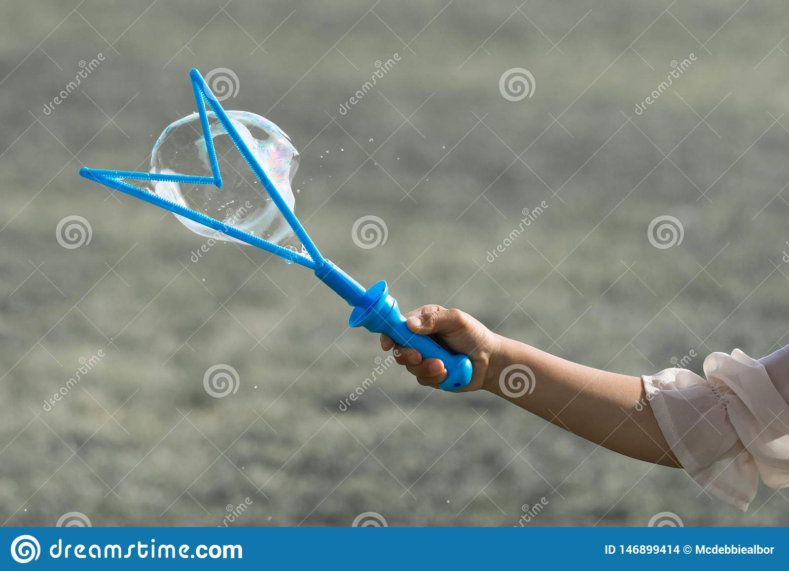 Een hand van een weinig jong meisje die een blauwe bellenmaker houden en borrelt maken