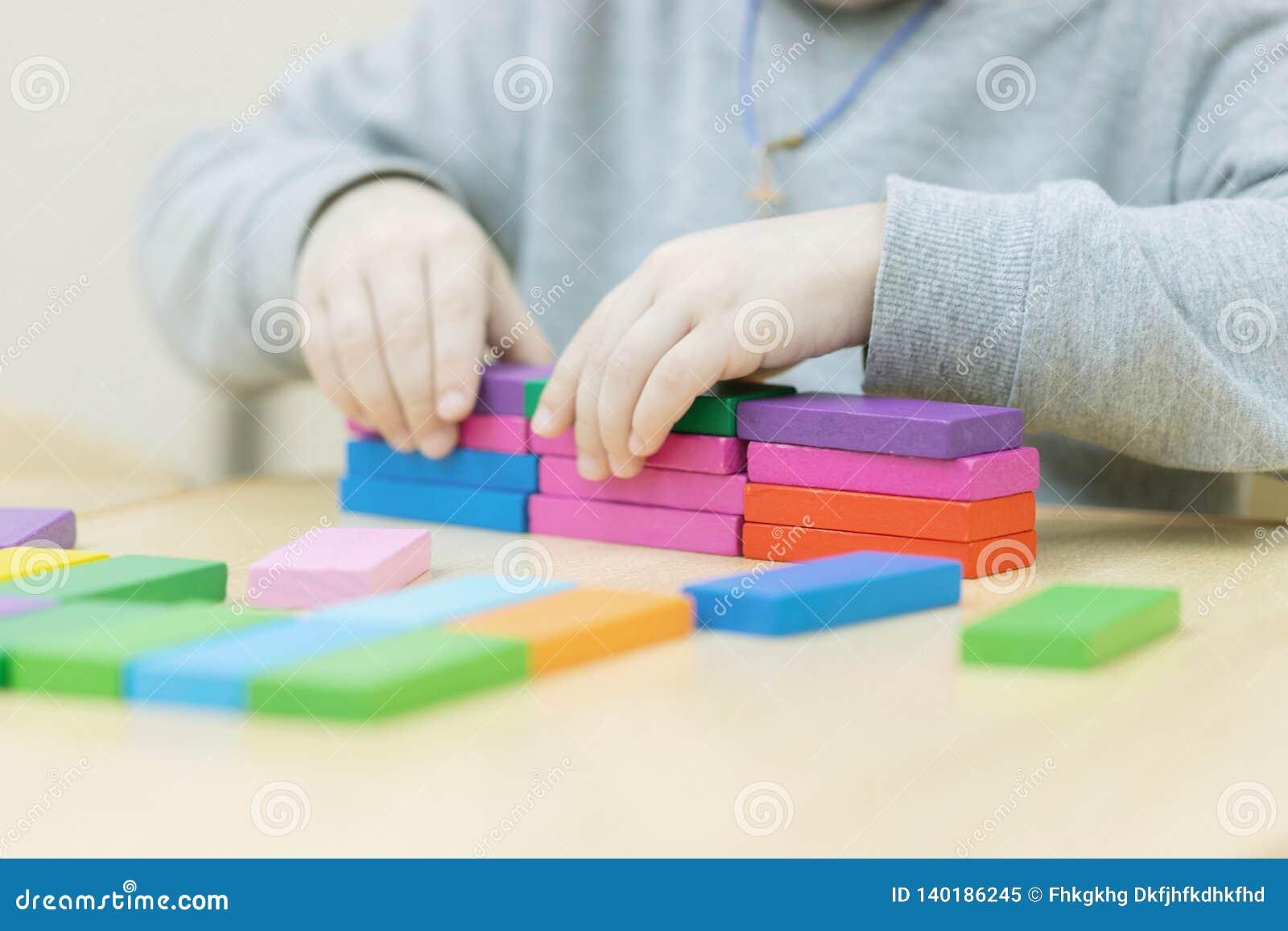 Een hand zet laatste kubus op de bovenkant van pyramide