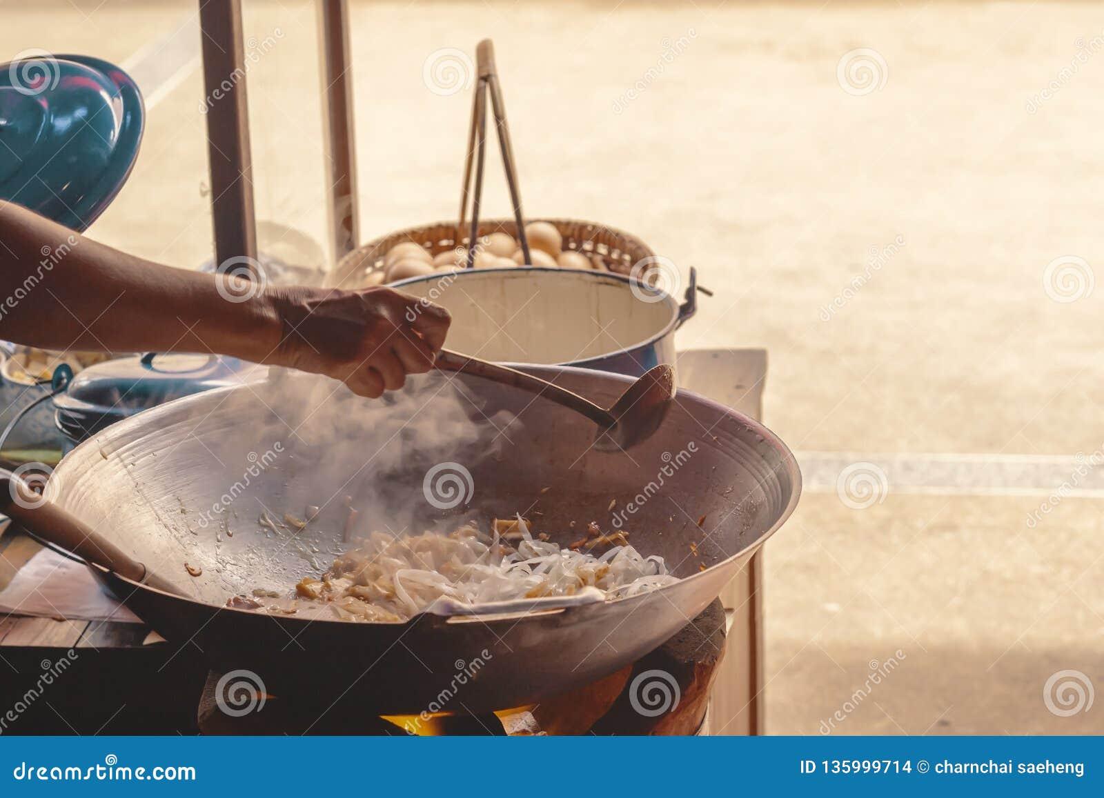 Een handchef-kok maakt Gebraden rijststokken met garnalen in straatvoedsel