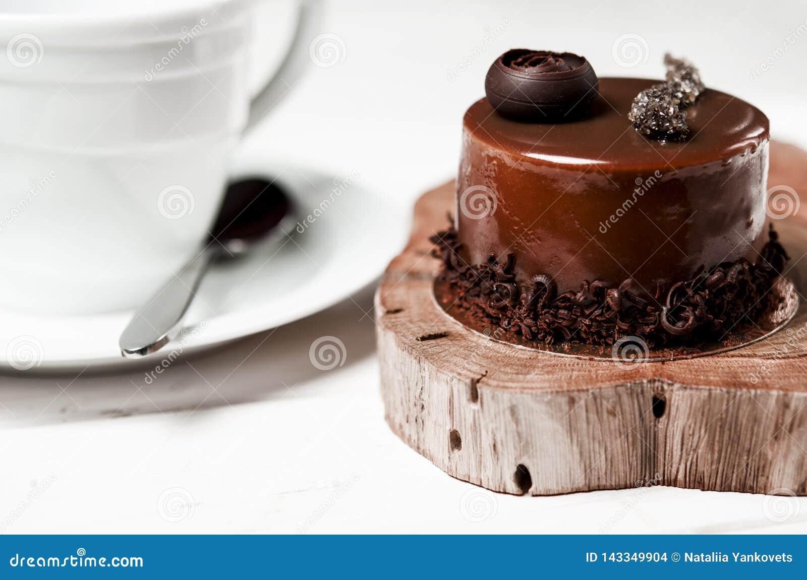Een heerlijke chocoladecake met chocoladestukken ligt op een houten tribune naast een witte kop, die zich op een witte lijst bevi