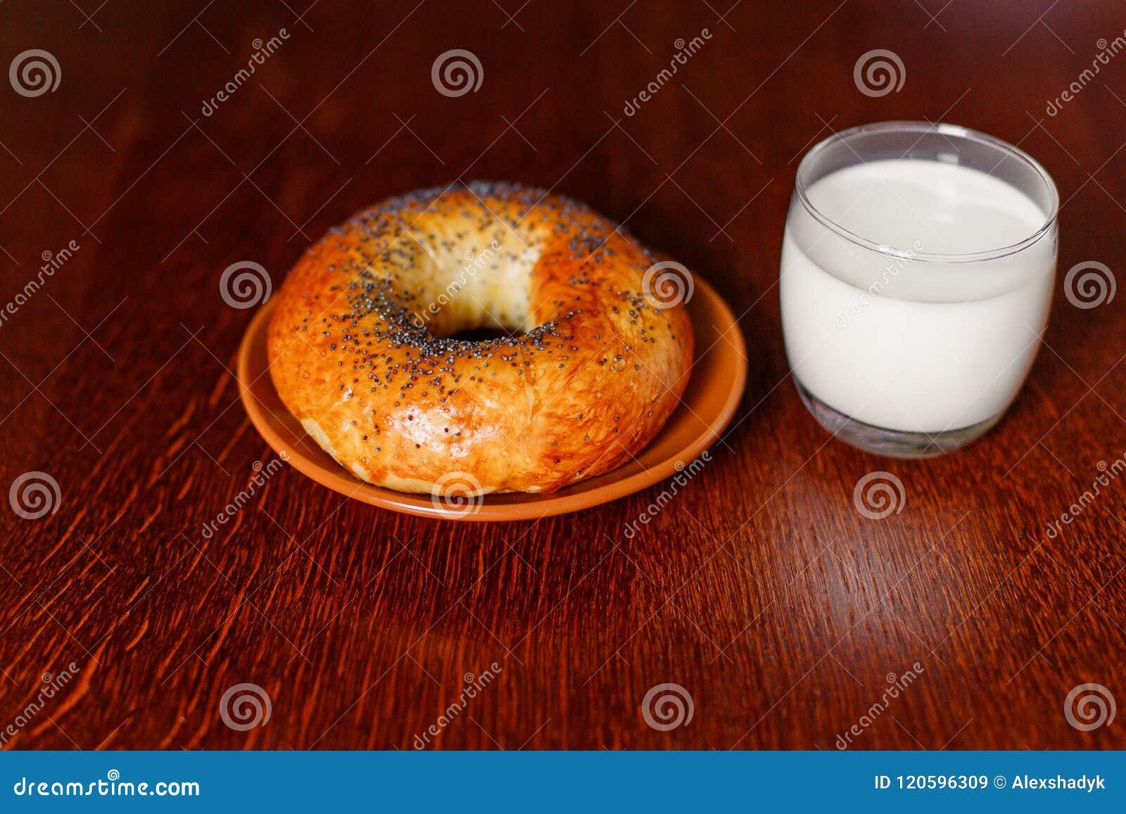 Een heerlijke ongezuurd broodje en een melk op een houten lijst