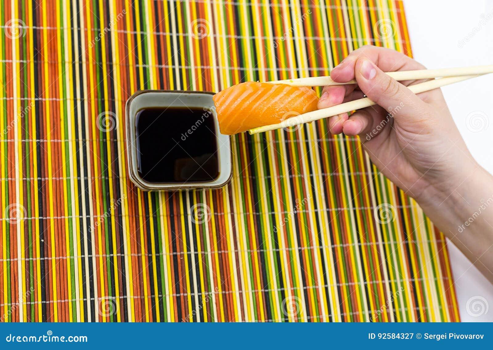 Een heerlijke sushirijst en een plak die van zalm, bamboestokken in zijn hand houden, worden verminderd in een kom met sojasaus o