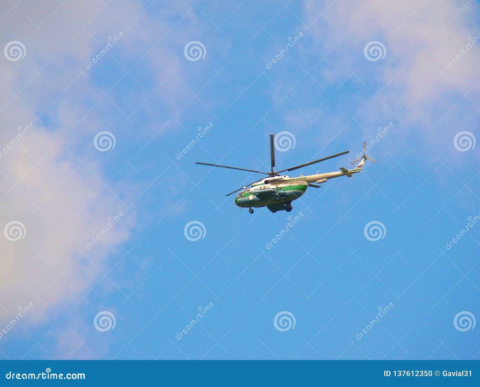 Een helikopter in de blauwe hemel onder de wolken