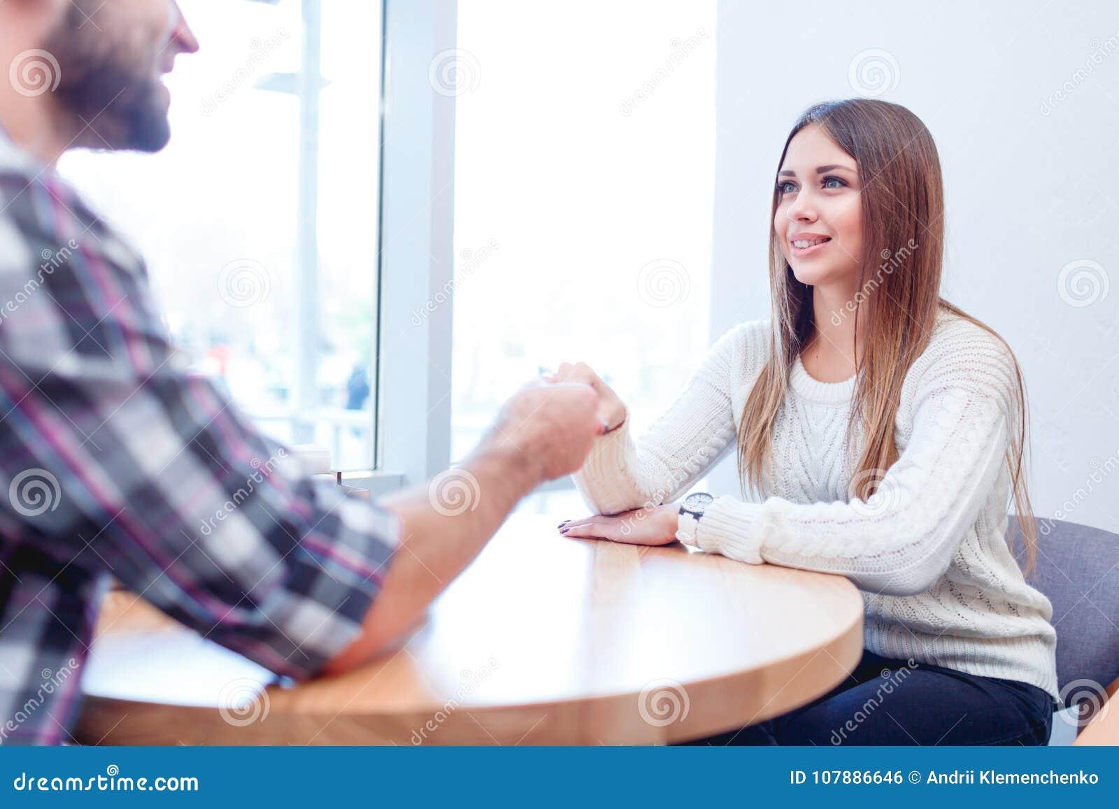 Een het houden van paarzitting in een koffie, holdingshanden en het bekijken veel liefs elkaar