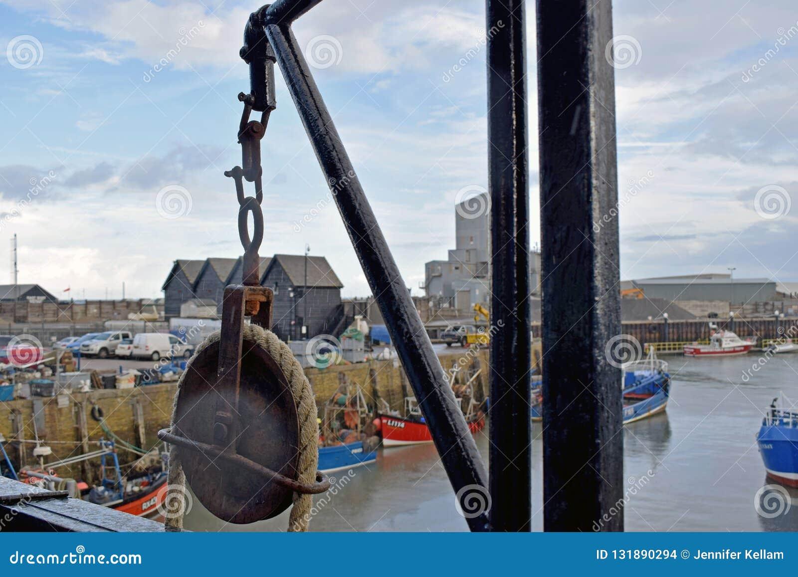 Een hijstoestel voor liftkratten wordt gebruikt vissen met haven op de achtergrond die