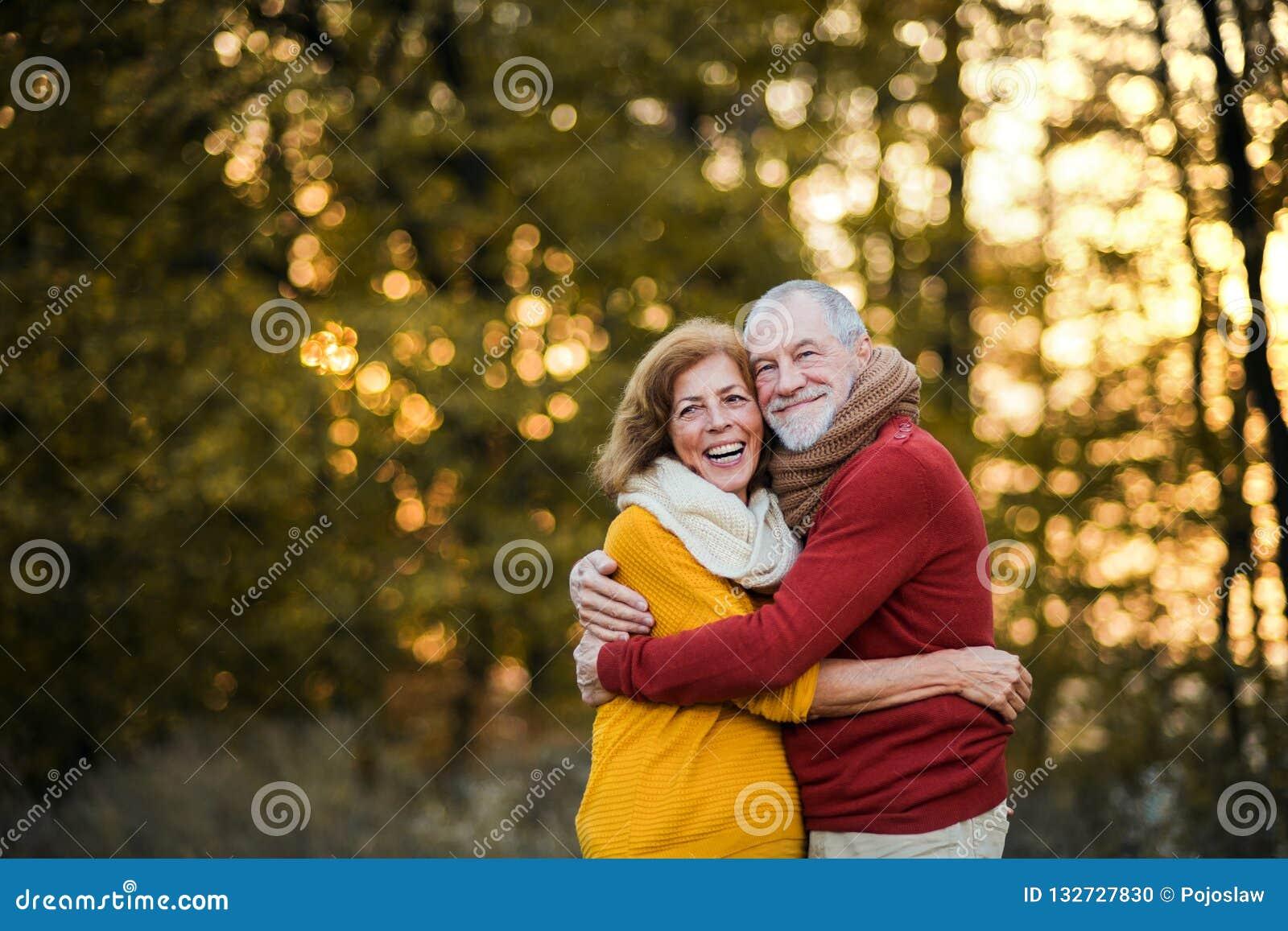 Een hoger paar die zich in een de herfstaard bij zonsondergang, het koesteren bevinden De ruimte van het exemplaar