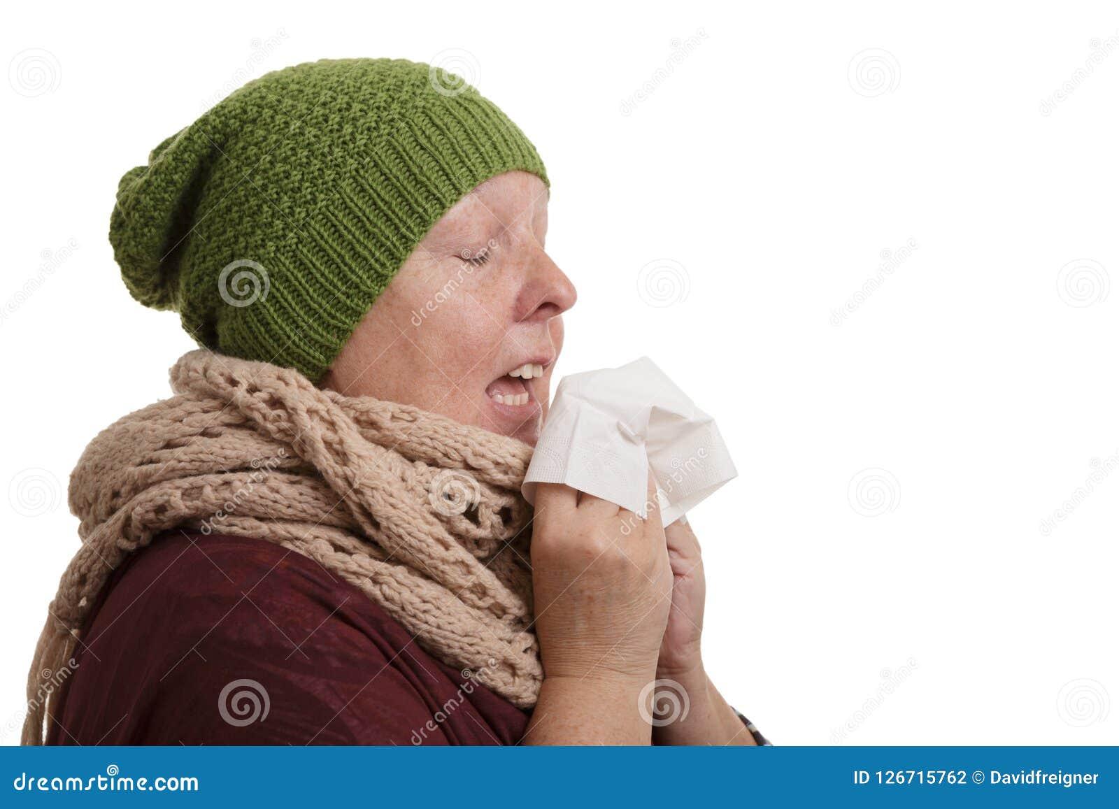 Een hogere vrouw in de wintertijd met ziekte moet niezen en blo