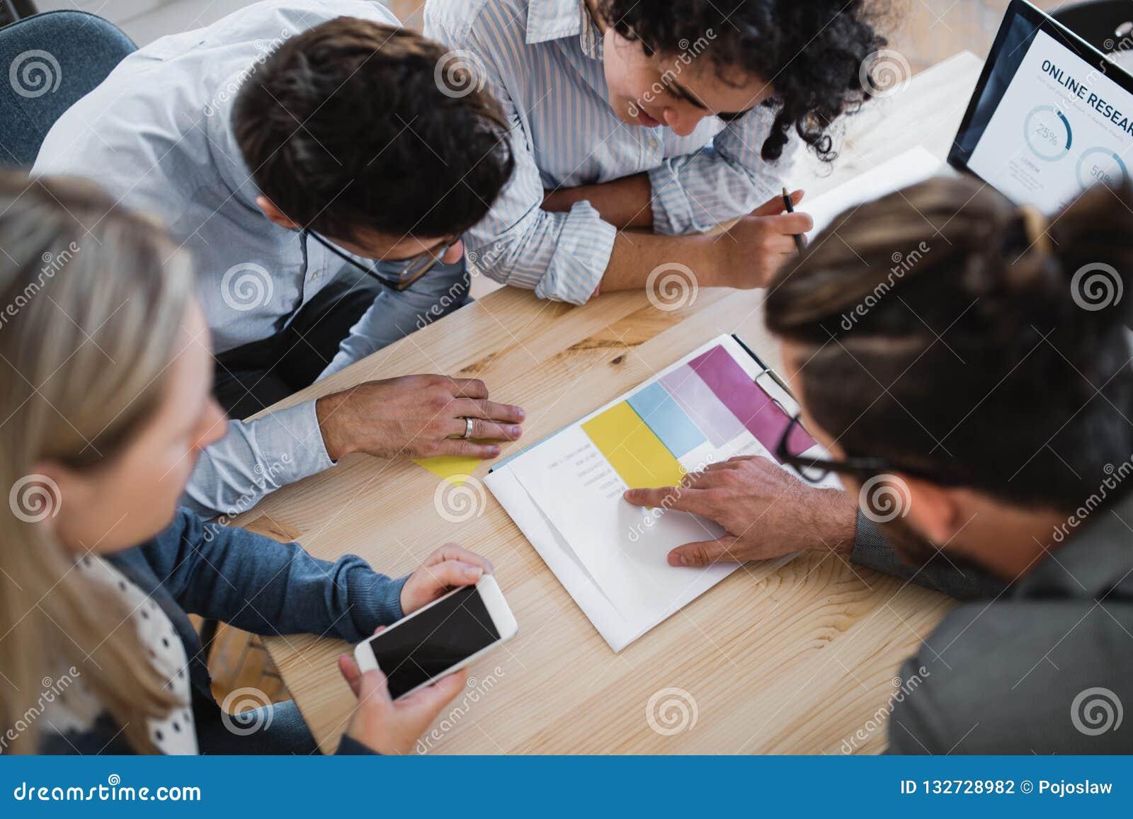 Een hoogste mening van groep jong zakenlui die in een modern bureau samenwerken