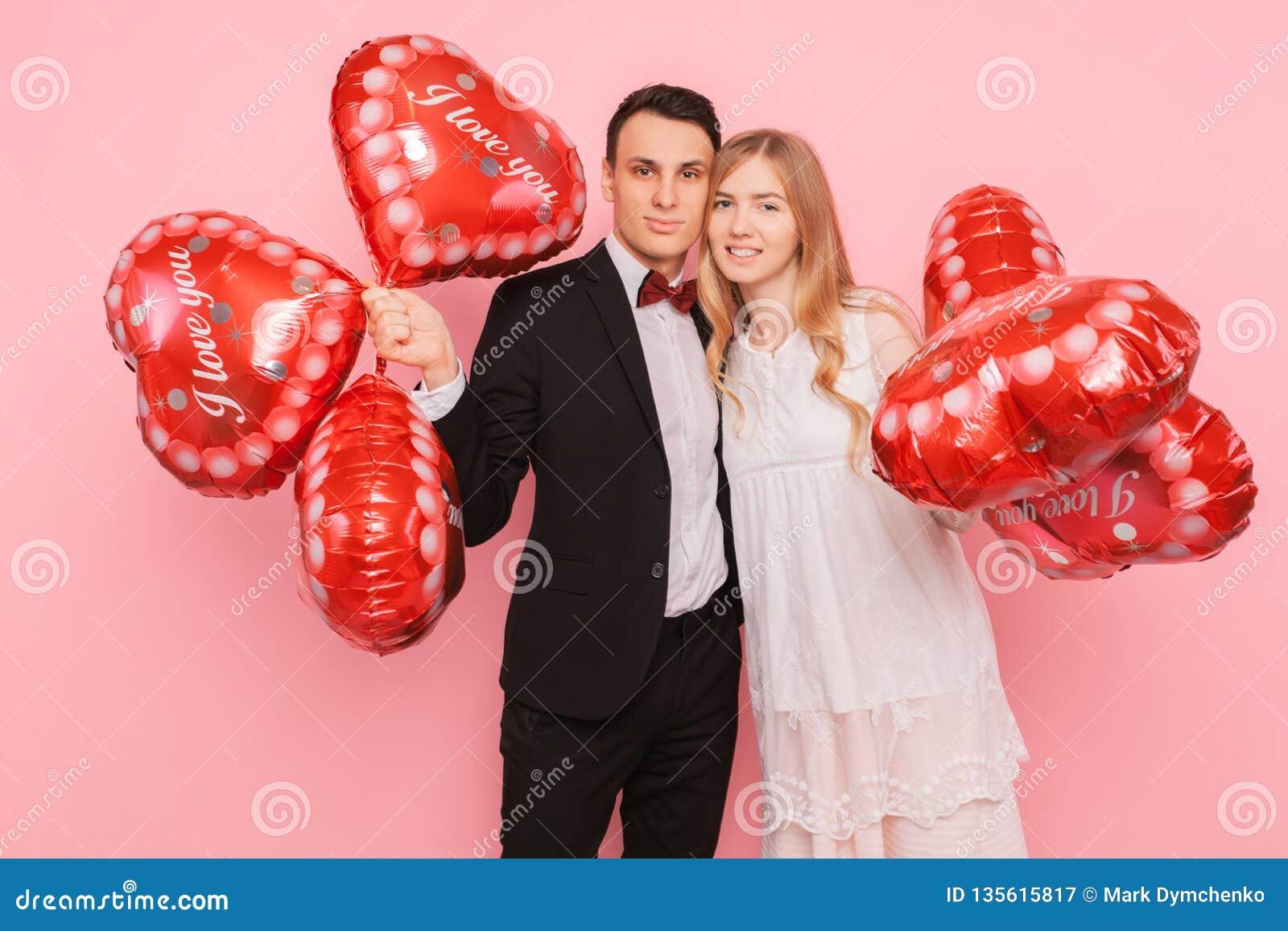 Een houdend van paar, een man en een vrouw, die hart-vormige ballons, in een studio op een roze achtergrond houden, concept voor
