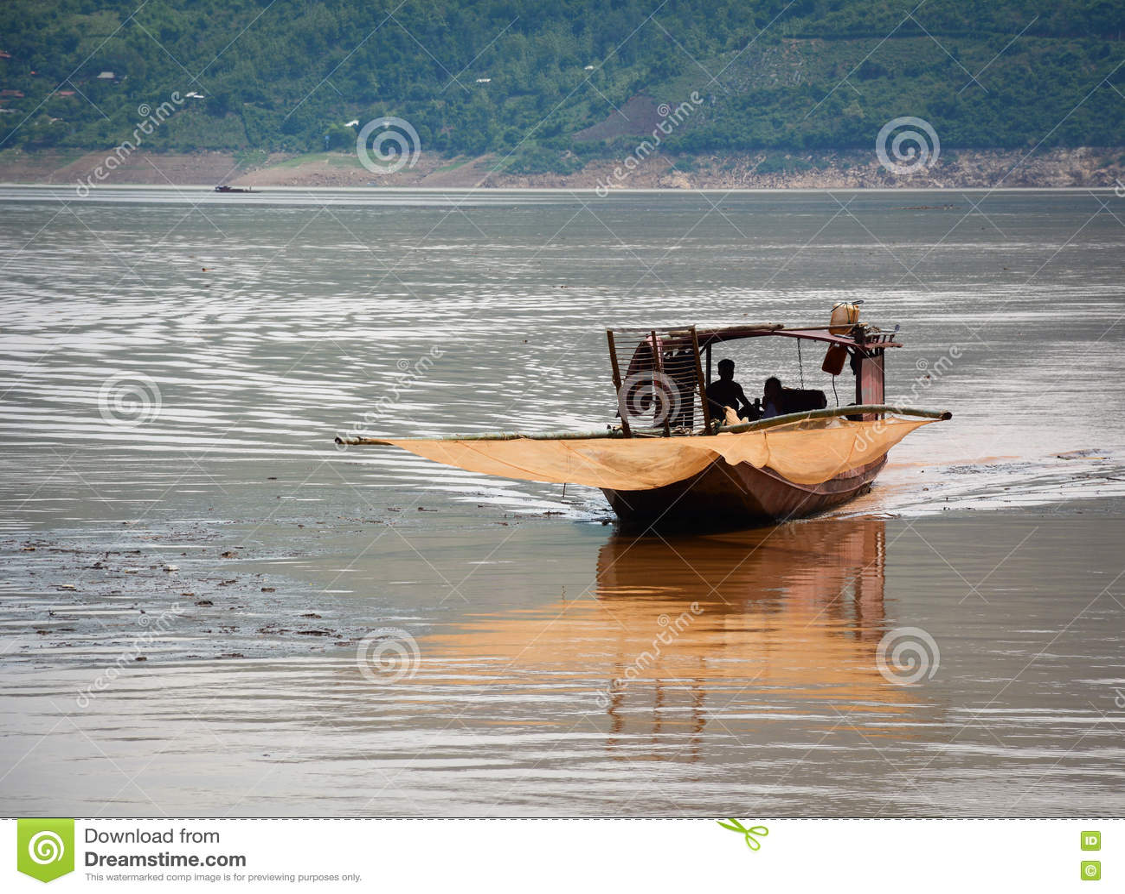 Een houten boot die op rivier met moutainachtergrond drijven in Moc CH