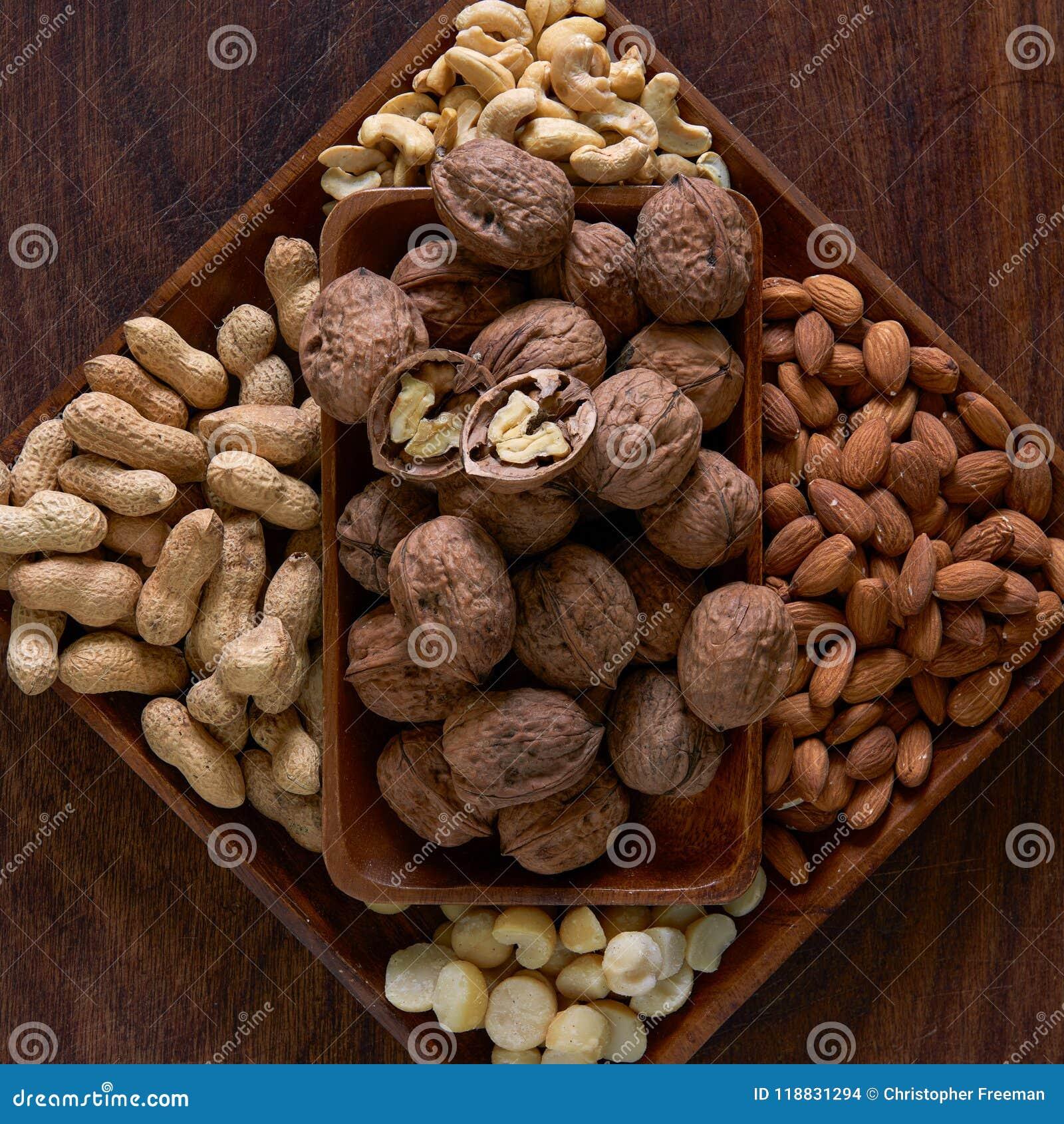Een houten komhoogtepunt van okkernoten, pinda s, amandelen, cachou en macadamias op een houten raad