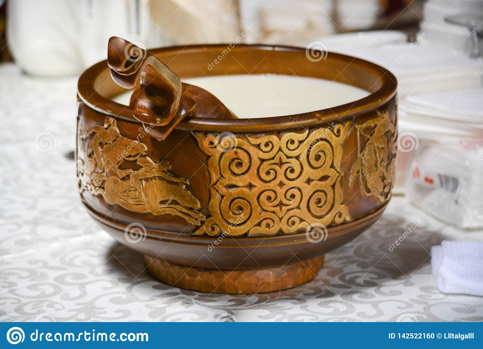 Een houten kop met de gietlepel van een nomade De melk wordt gegoten in de kop Cultureel erfgoed van de Kazakh mensen