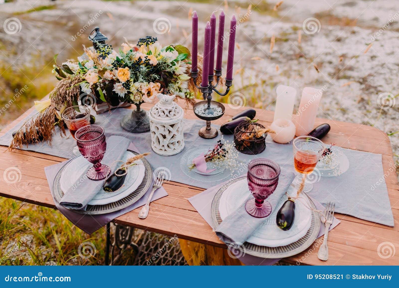 Een houten lijst wordt gediend voor twee, op de lijst zijn er samenstellingen van bloemen, kaarsen, bestek en glazen voor wijn