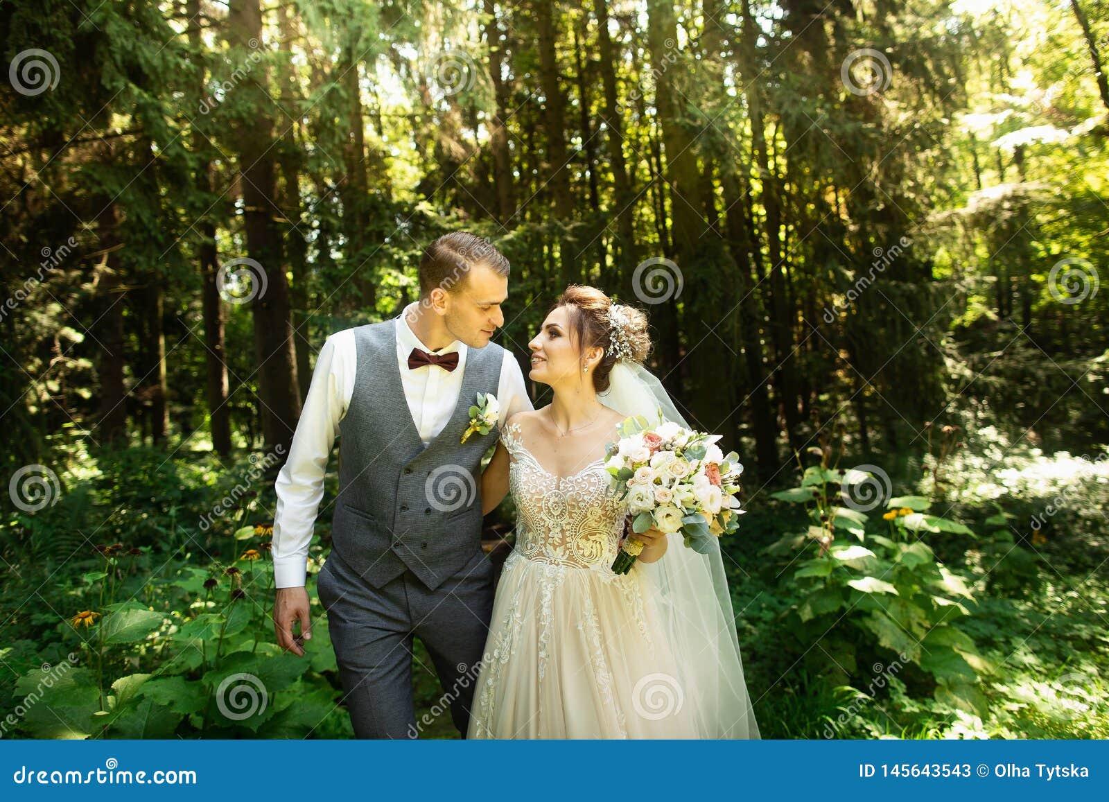 Een huwelijkspaar geniet van lopend in het hout De jonggehuwden koesteren en houden handen