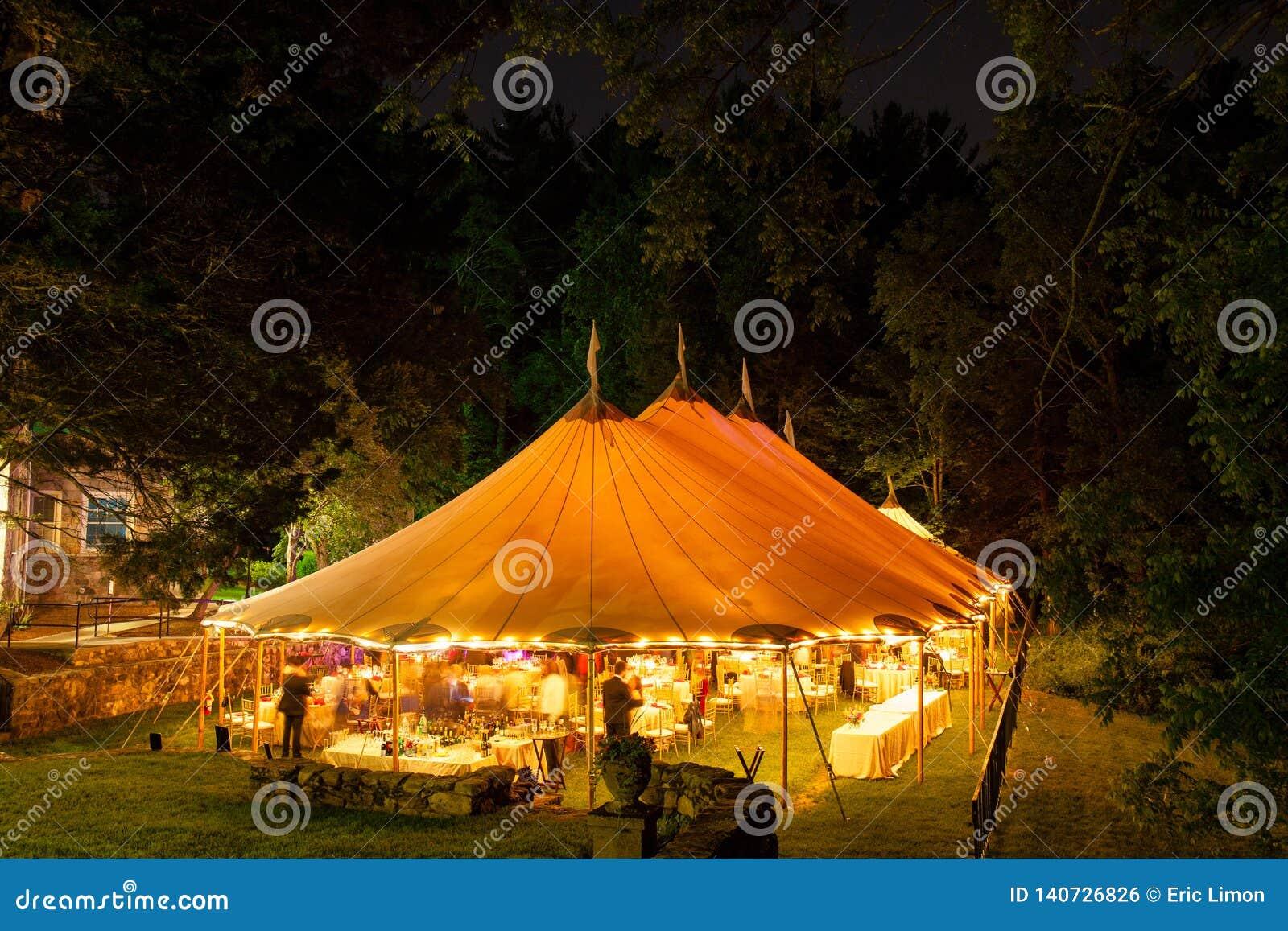 Een huwelijkstent bij nacht door bomen met een oranje gloed van de lichten wordt omringd, lange blootstelling - de reeks die van