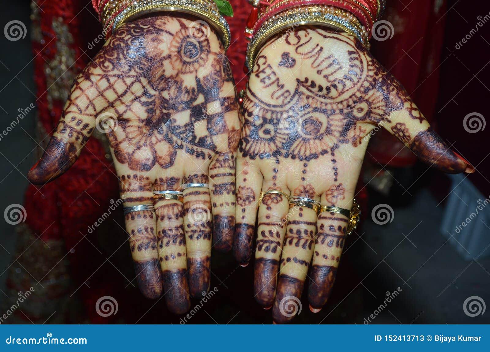 Een Indische bruidegom die haar hand met het mooie mehndi desing toont tijdens huwelijk