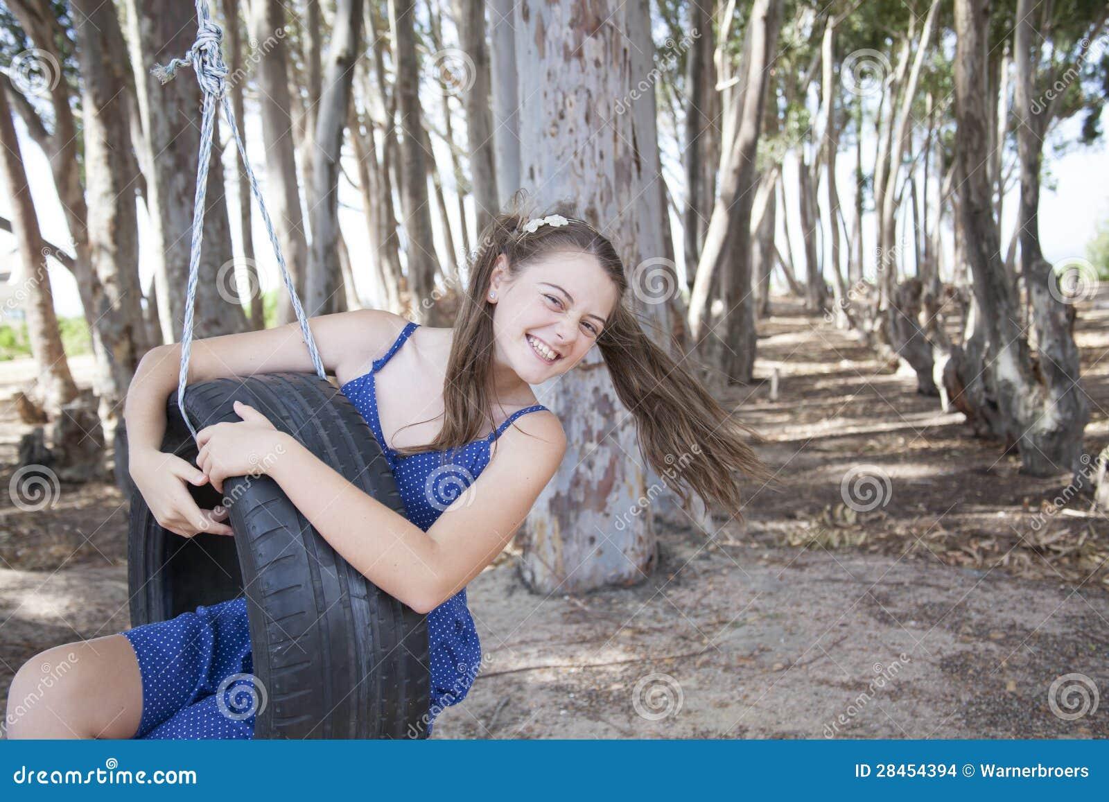 Een jong aantrekkelijk meisje die met een bandschommeling spelen
