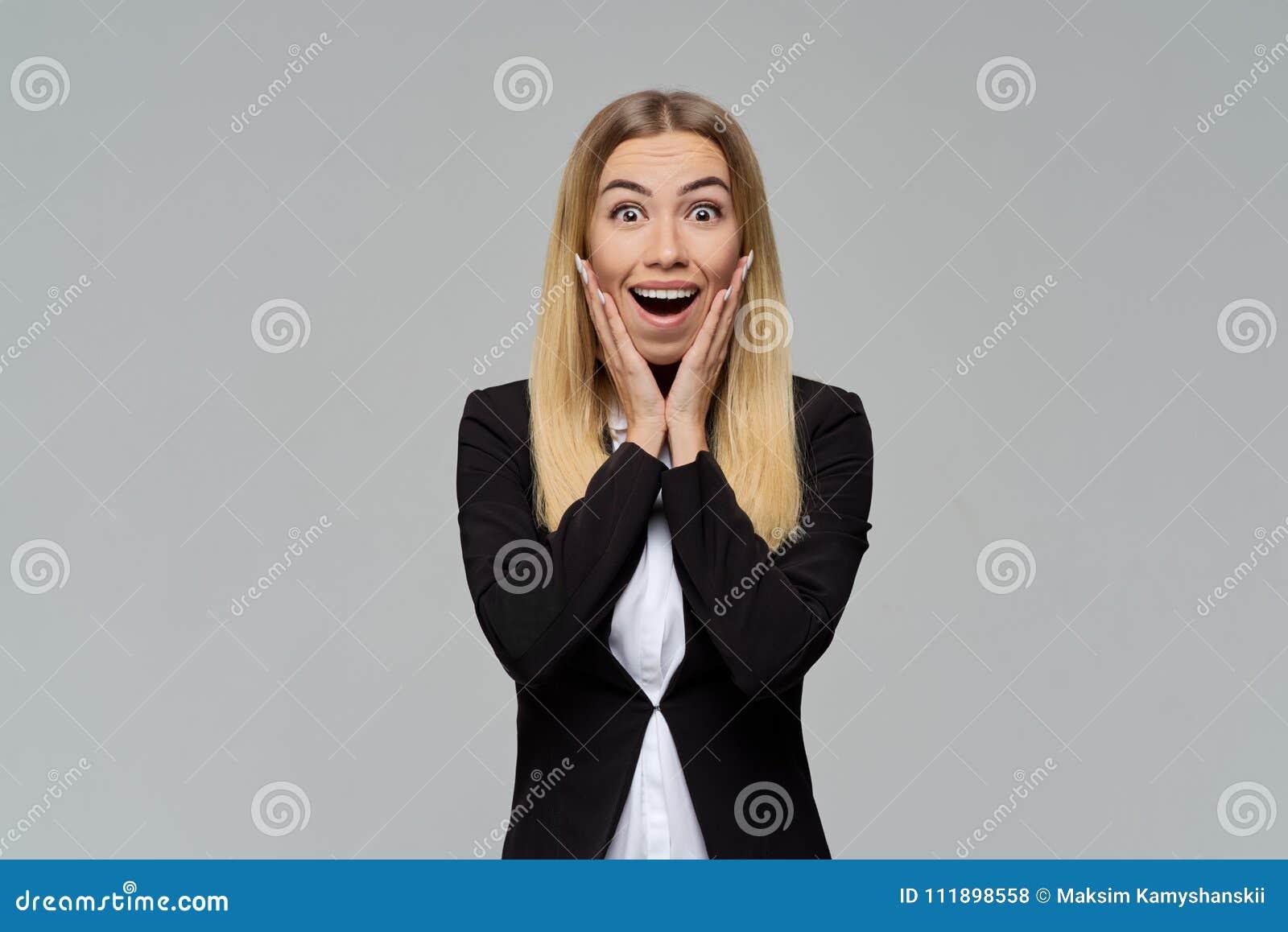 Een jong blondemeisje in een pak en een witte blouse opent wijd verrassend haar ogen en mond
