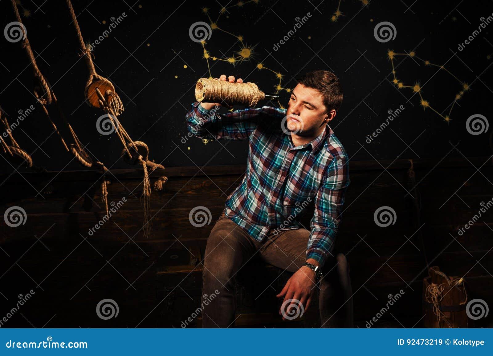 Een jong mannetje zit op een borst, onderzoekend glasfles en tryi