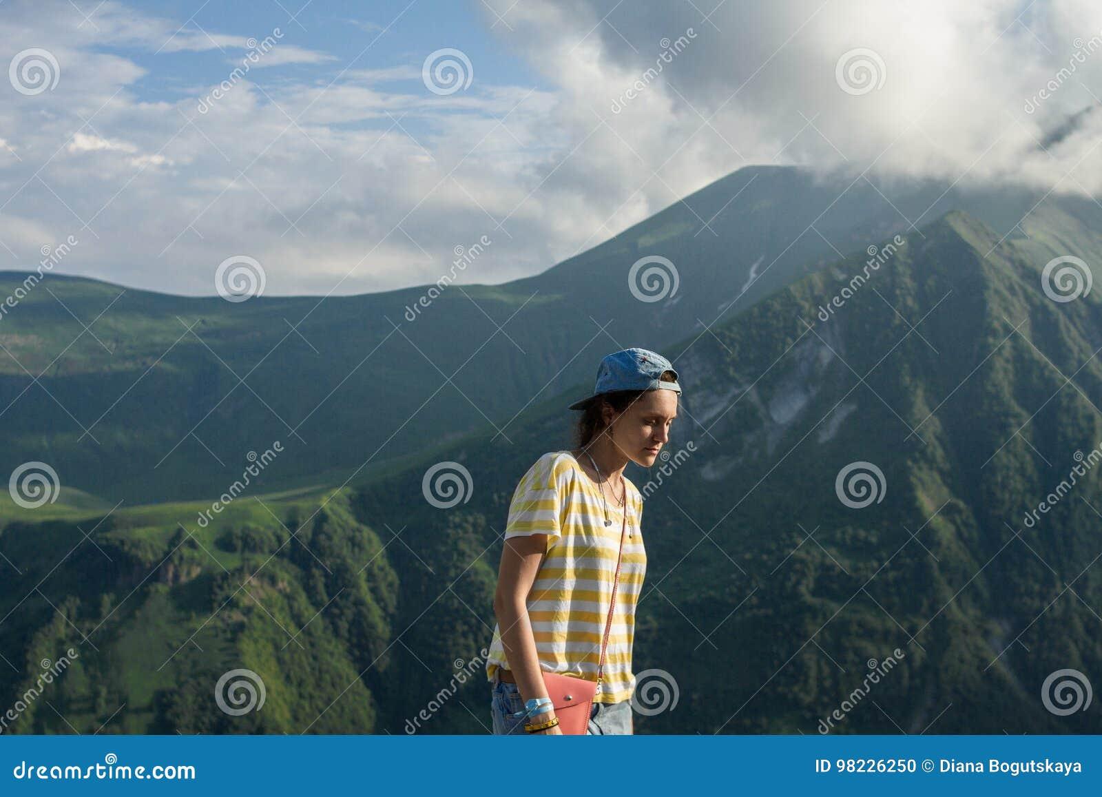 Een jong meisje in een gestreepte T-shirt en een GLB in de zomer op de sprookjebergen en een geheimzinnige hemelachtergrond