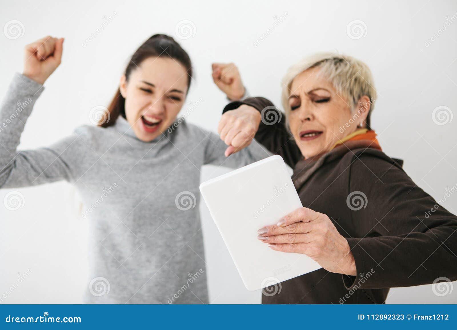 Een jong meisje en een bejaarde bekijken iets die op de tablet interesseren en tonen emoties Gezamenlijke mededeling,
