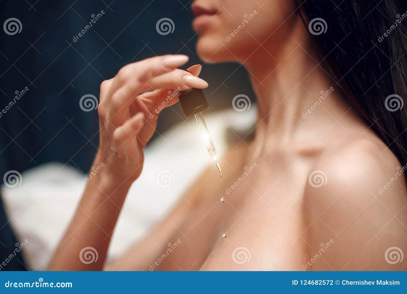 Een jong meisje houdt een pipet met kosmetische olie De zorgconcept van de huid