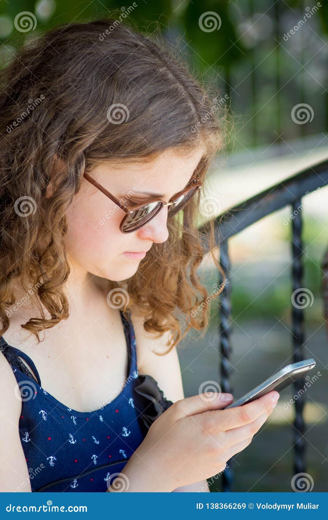 Een jong meisje houdt een telefoon in haar handen Mededeling die een smartphone gebruiken Modern vermaak op Internet_