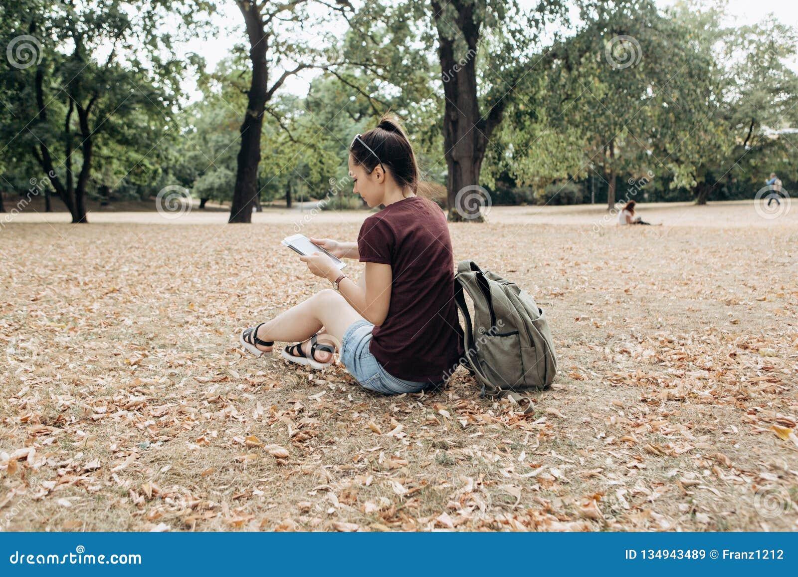 Een jong meisje met een rugzak zit in het de herfstpark en gebruikt de tablet