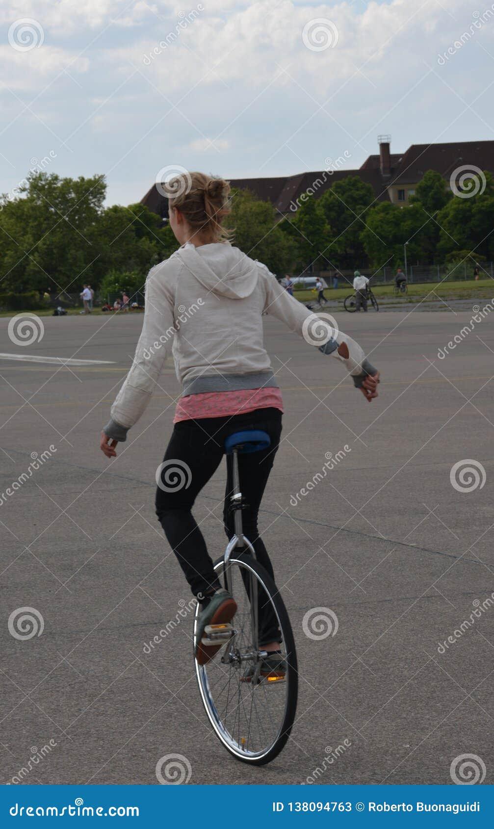 Een jong meisje op fiets met slechts één wiel