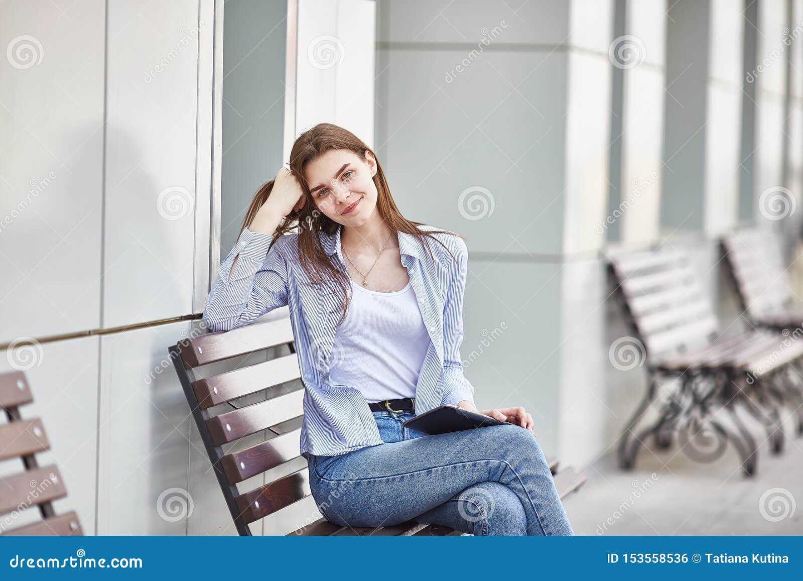 Een jong meisje zit op een bank met een tablet in haar handen en het glimlachen