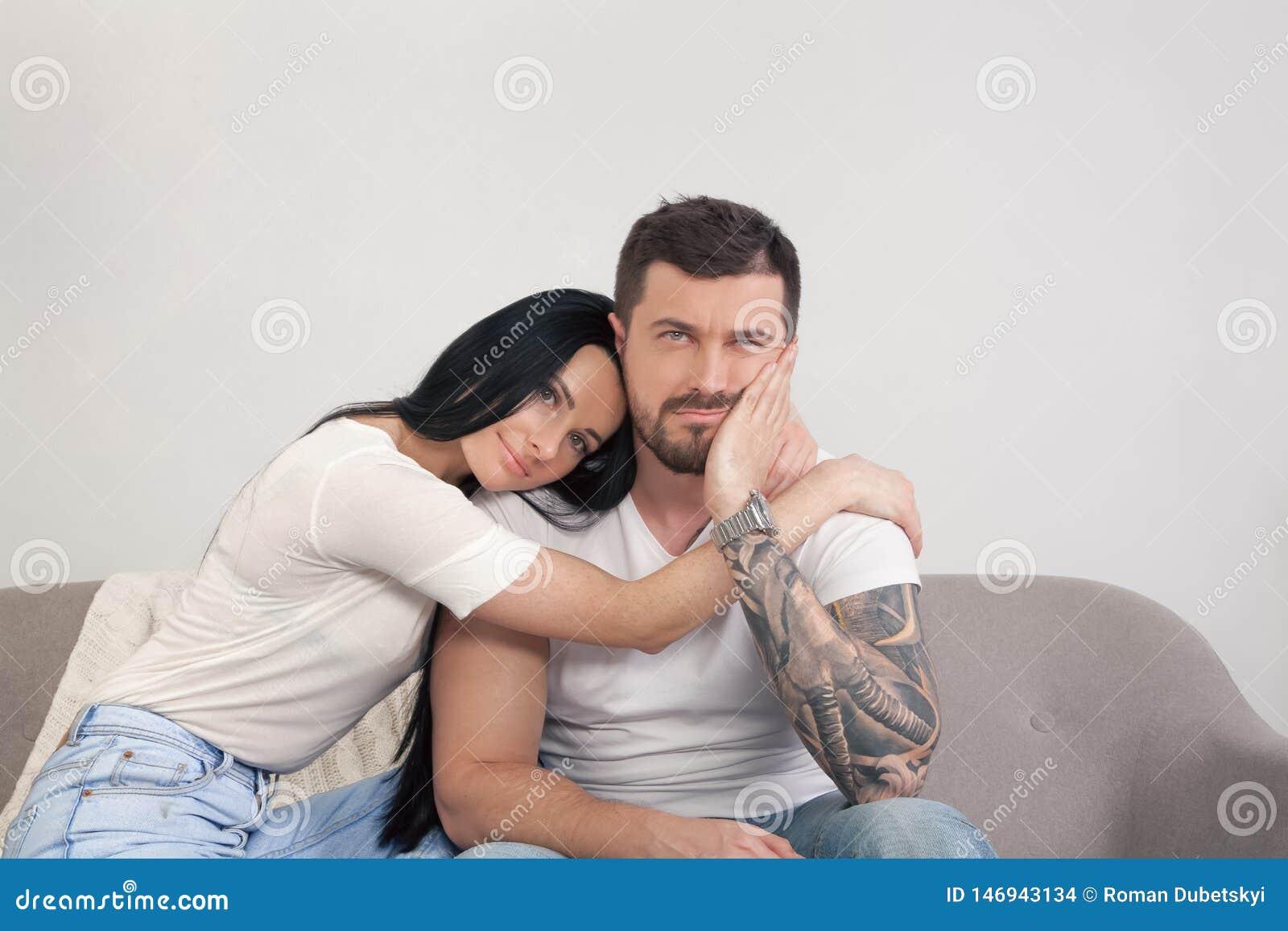 Een jong mooi meisje troost haar vriend die zittend teleurstelt Hij verloor zijn baan en is droevig