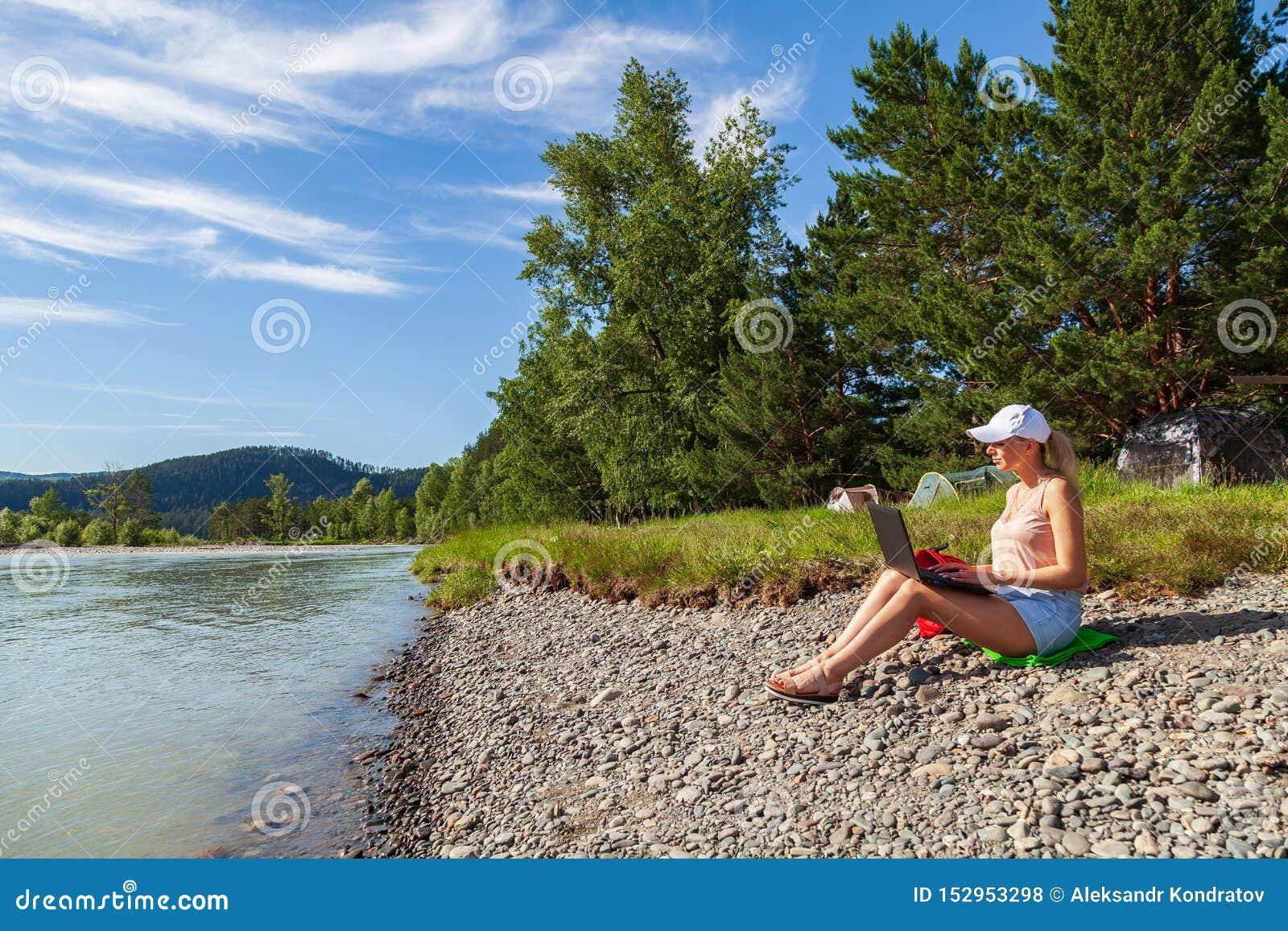 Een jong mooi vrouwenblonde in de borrels van een wit GLB en van het denim zit op de rotsachtige kust van de rivier met laptop op