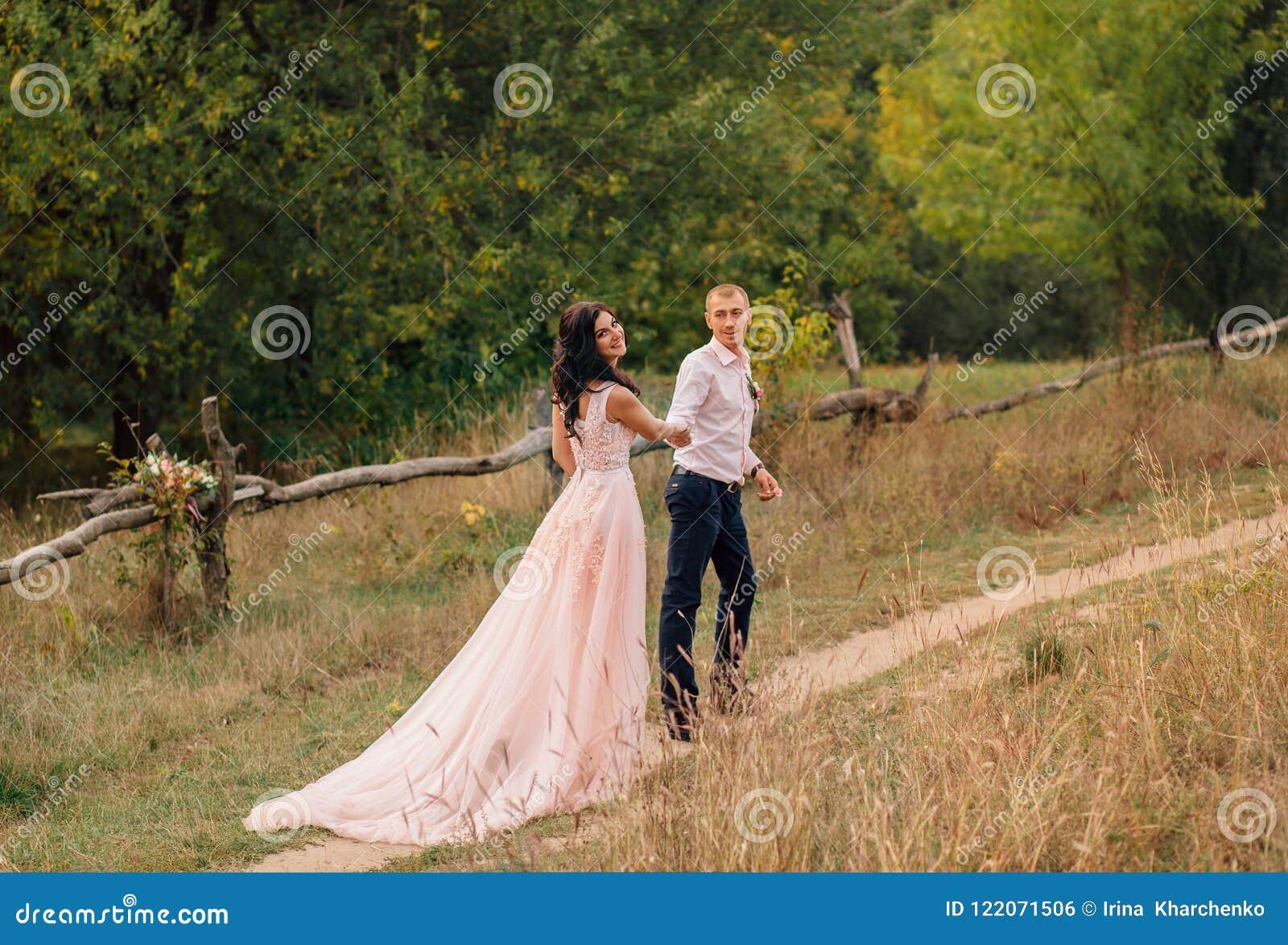 Een jong paar aan het begin van de het levensweg van samen het leven, bevindt zich symbolically tegen de achtergrond van a