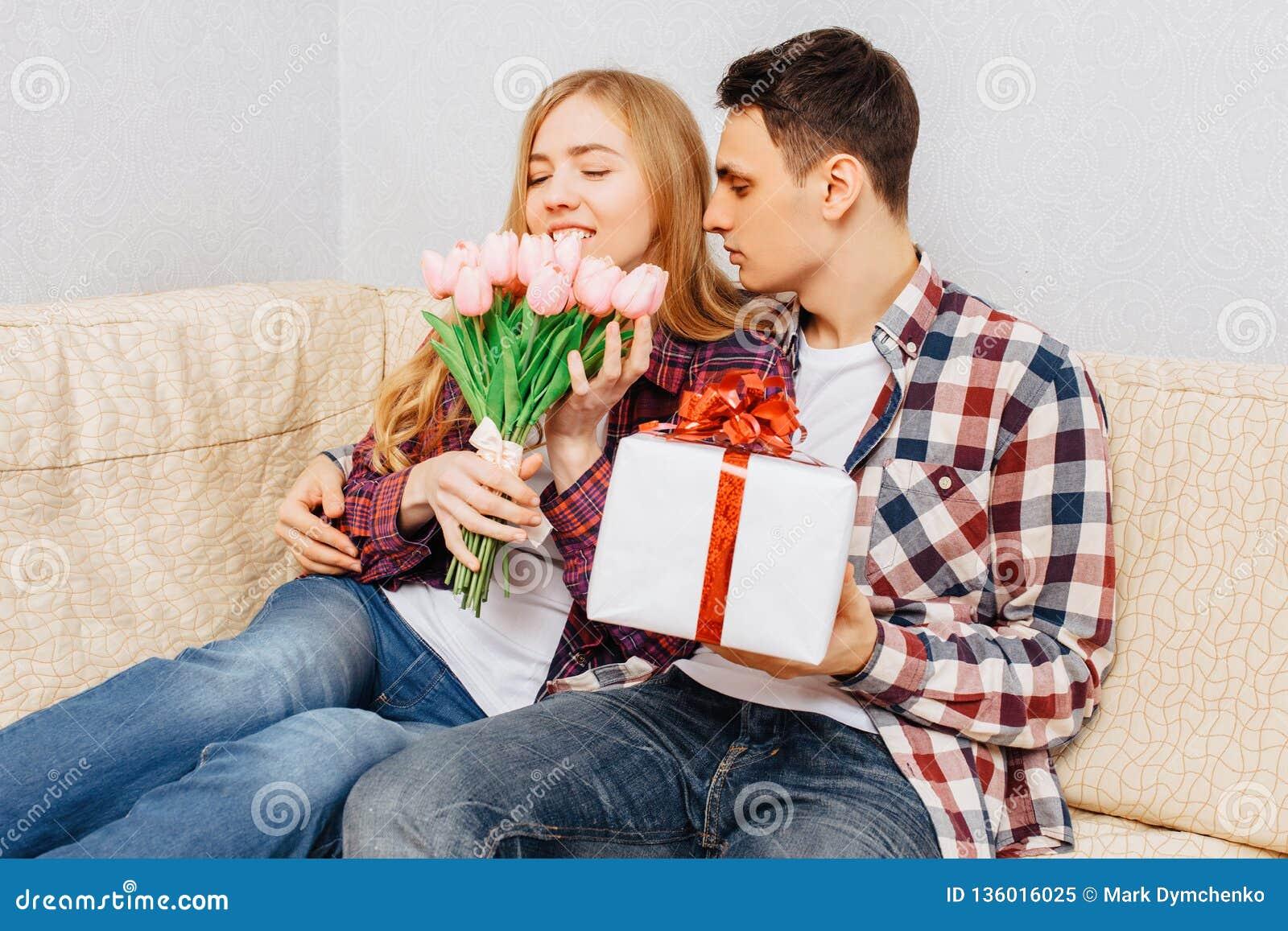 Een jong paar in liefde, een man wenst een vrouw door haar een boeket van tulpen en een gift geluk te geven, thuis zittend met de