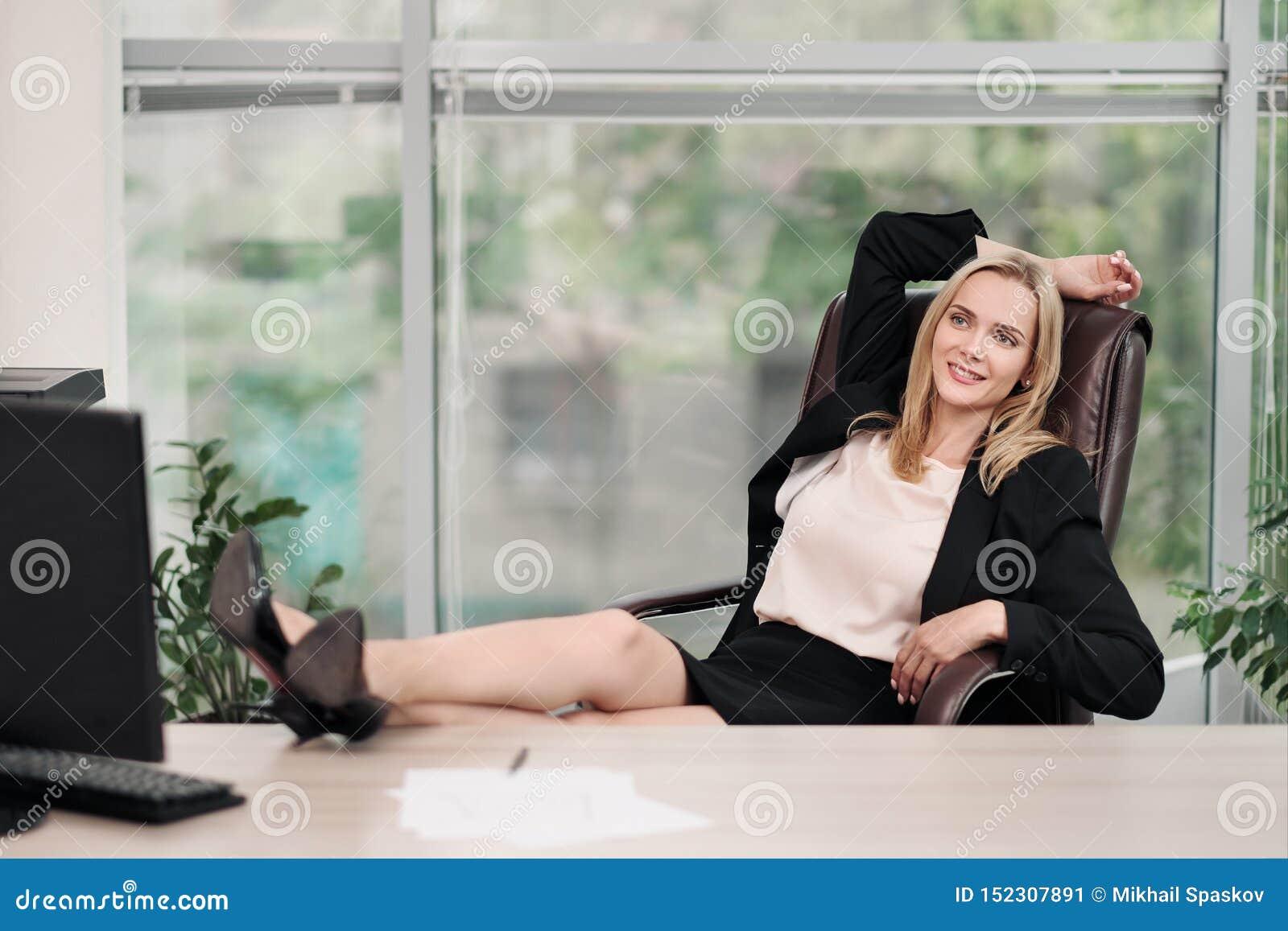 Een jonge aantrekkelijke vrouw in pak zit bij een bureau Rekt zich en ontspant op stoel uit De voeten zijn op lijst Rust van