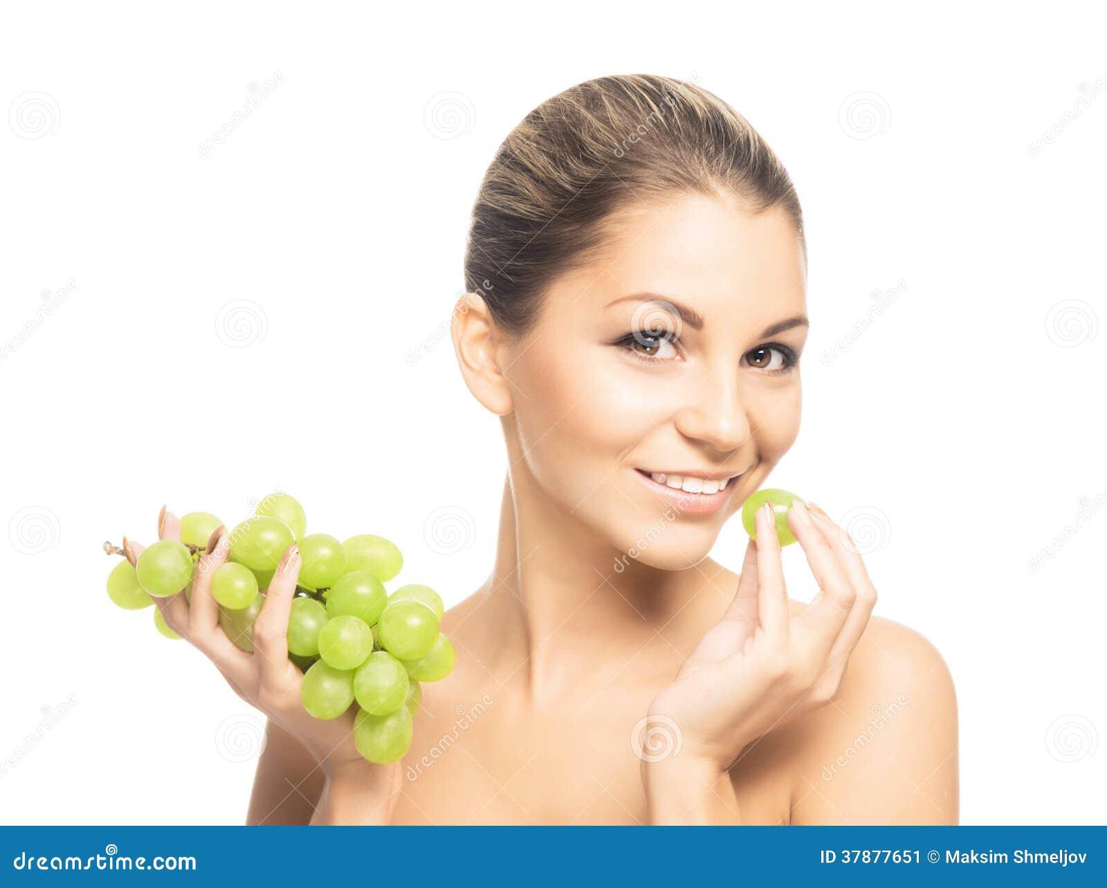 Een jonge en gelukkige vrouw die druiven eten