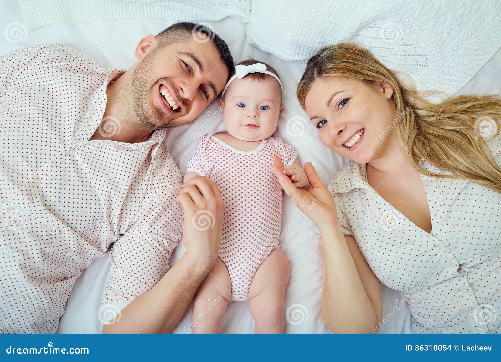 Een jonge familie met baby op bed Mening van hierboven
