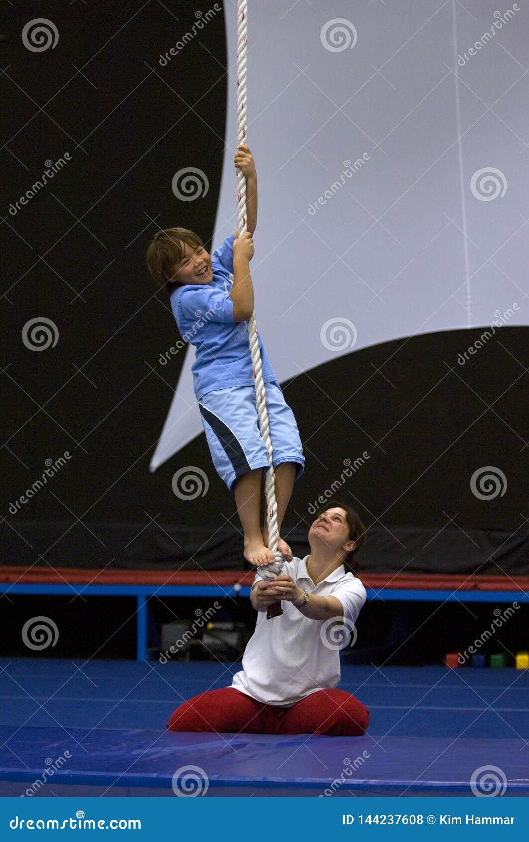 Een jonge jongen leert om een kabel in n-acrobaatschool te beklimmen