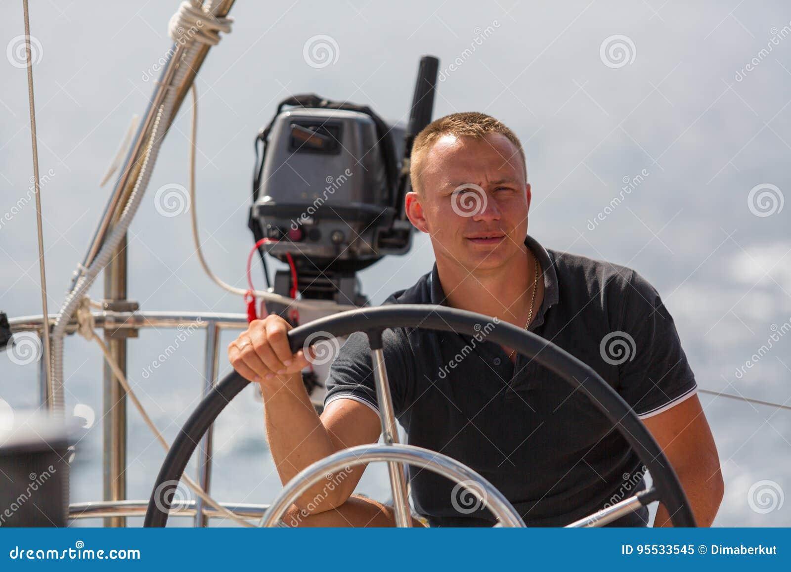 Een jonge kapitein bij het roer van een varend schip Sport